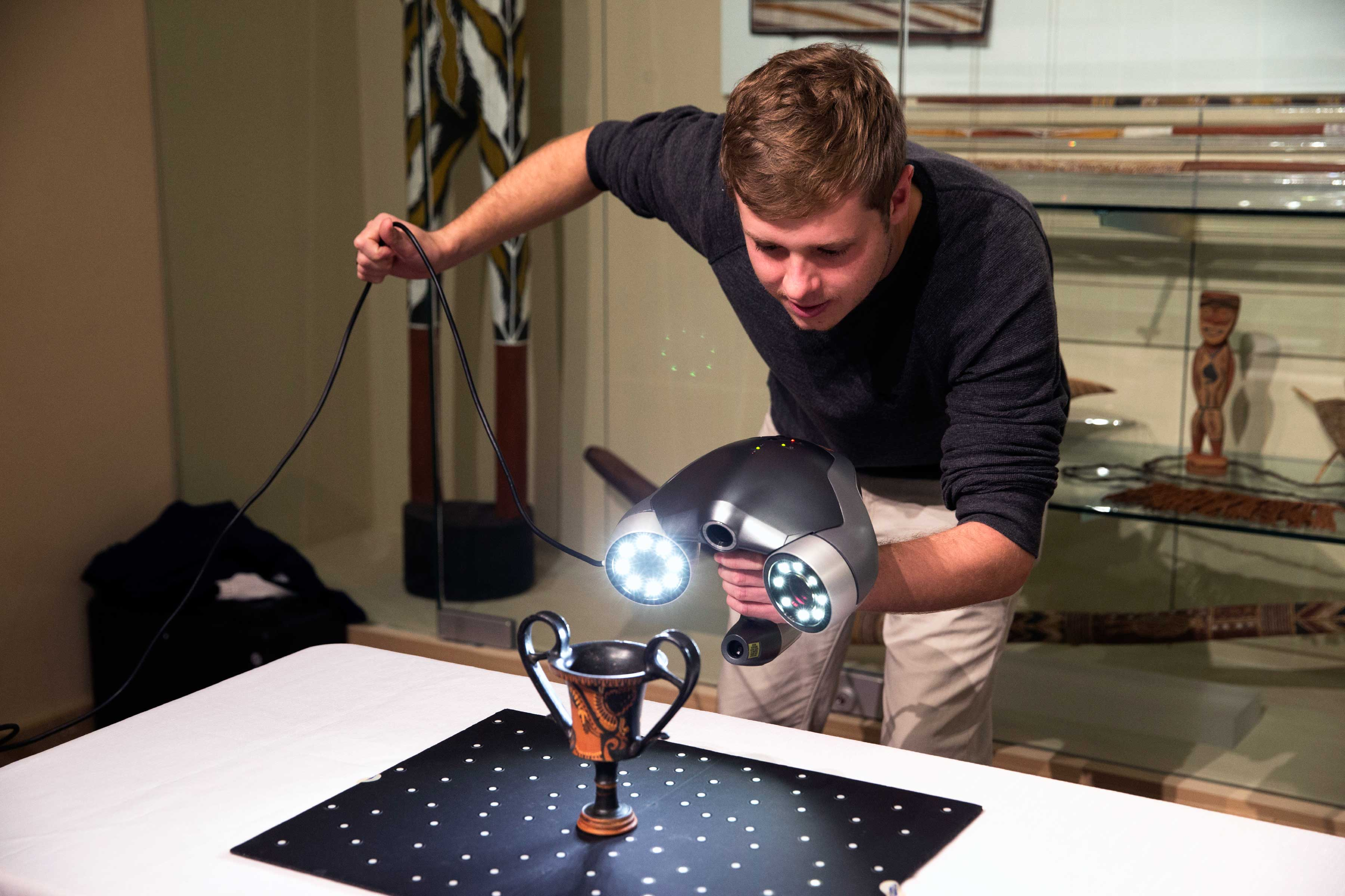 Lewis aims a 3-D scanner at a fourth-century vase atop a reflective mat that provides reference points for the scanner to build a virtual 3-D space. (Photo by Dan Addison, University Communications)