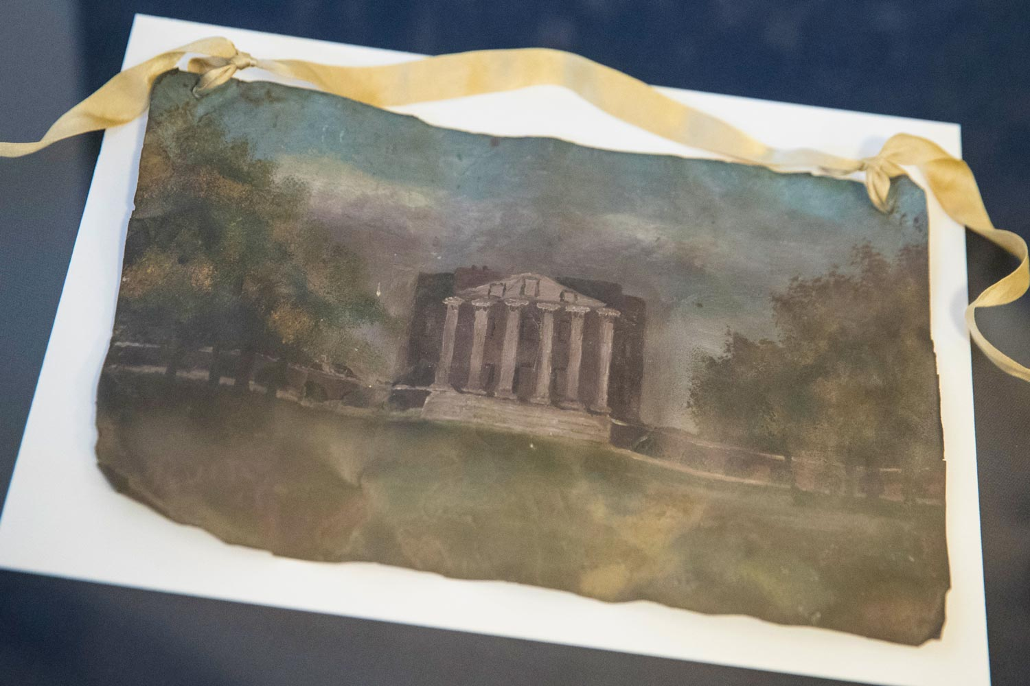 An image of the UVA Rotunda painted on a roof tile in a display case
