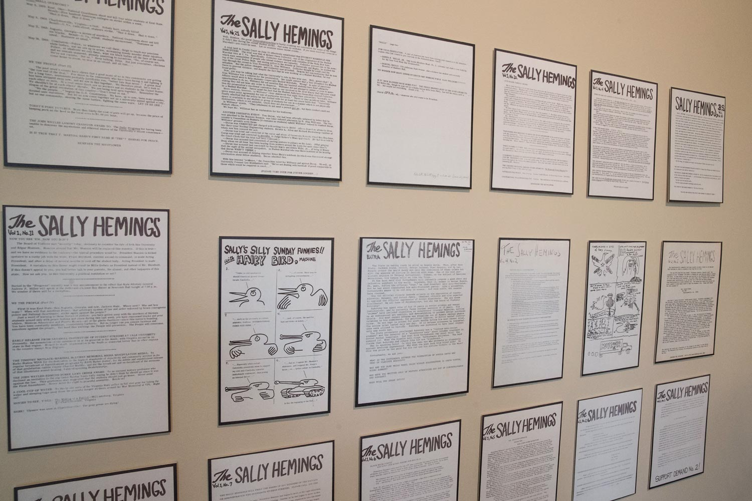 Three rows of black and white flyers mounted on a wall