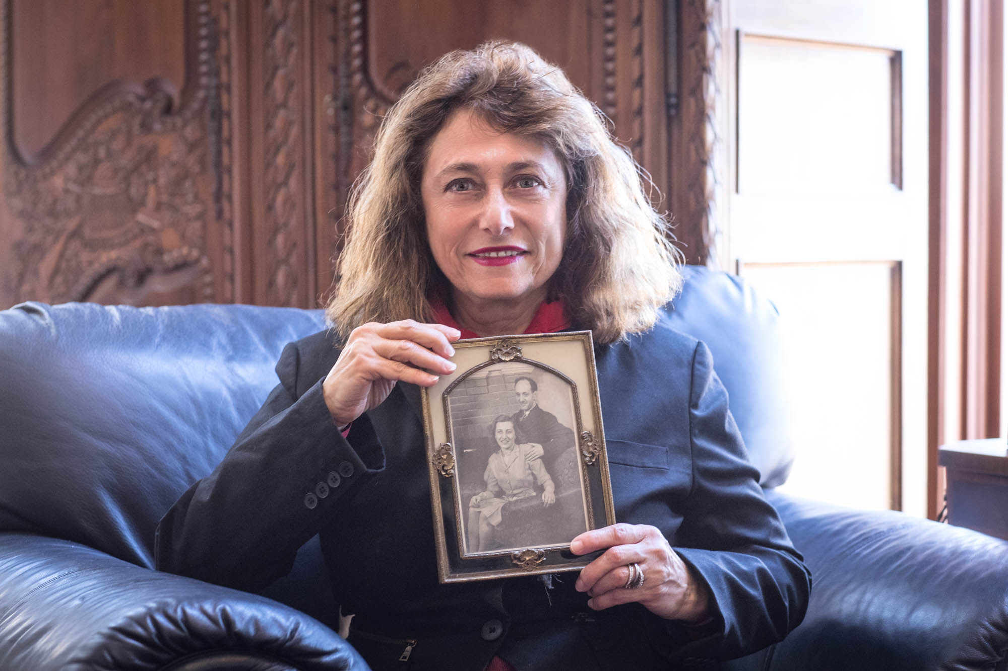 Adrienne Weinberger holds a photo of her parents. At the time of the attack, Marta Weinberger worked for the Army and Samuel Weinberger designed naval ships. (Photo by Sanjay Suchak, University Communications)
