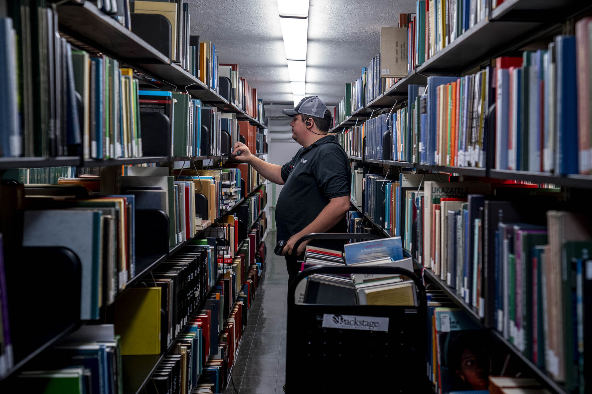 David Scott of Backstage Library Works selects a section of books in a particular call number as part of the process of moving them out of Alderman.