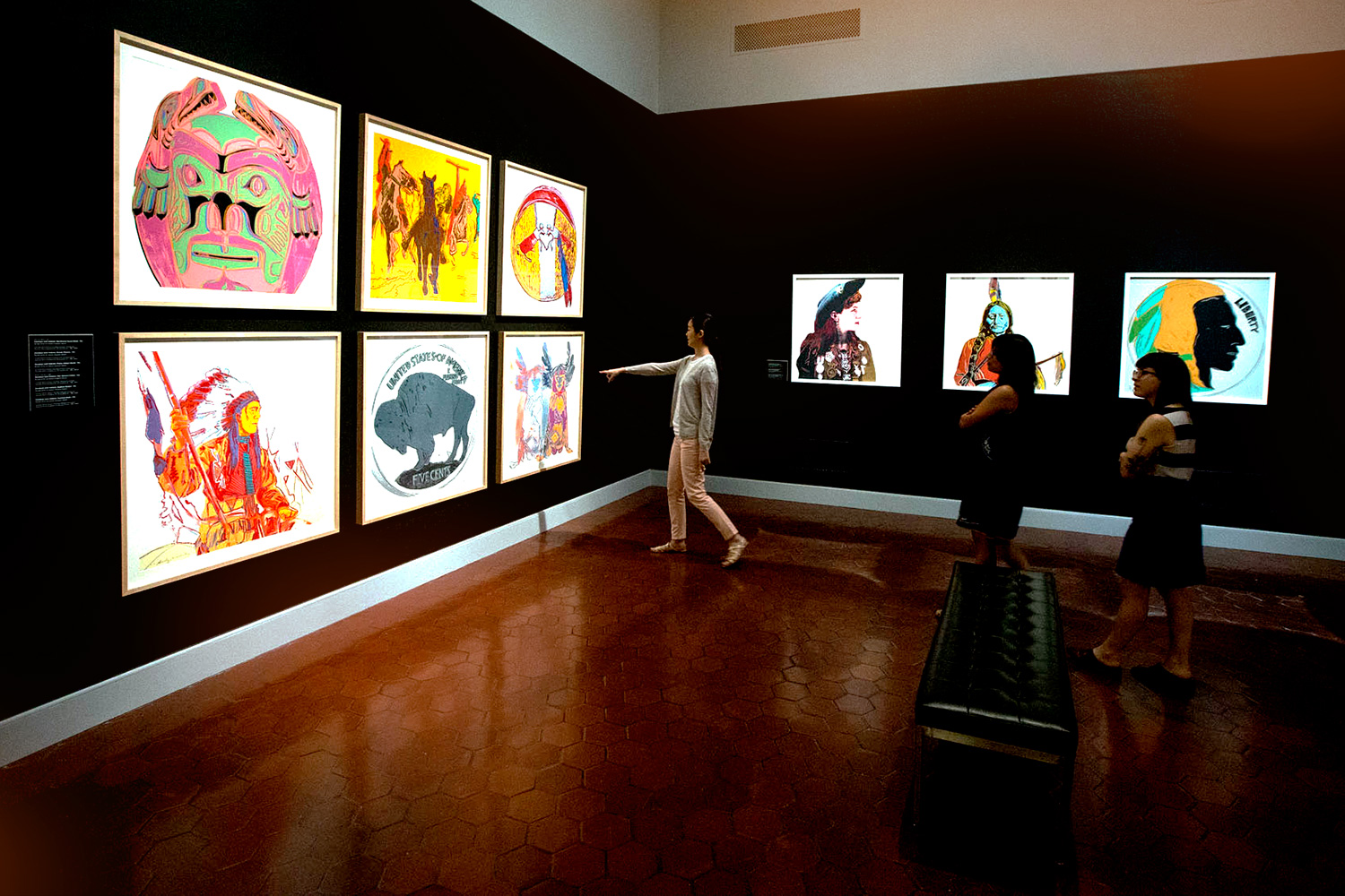 "The exhibition reunites Warhol's ""Cowboys and Indians"" series, including prints of figures like Annie Oakley and Sitting Bull, both seen here on the back wall."