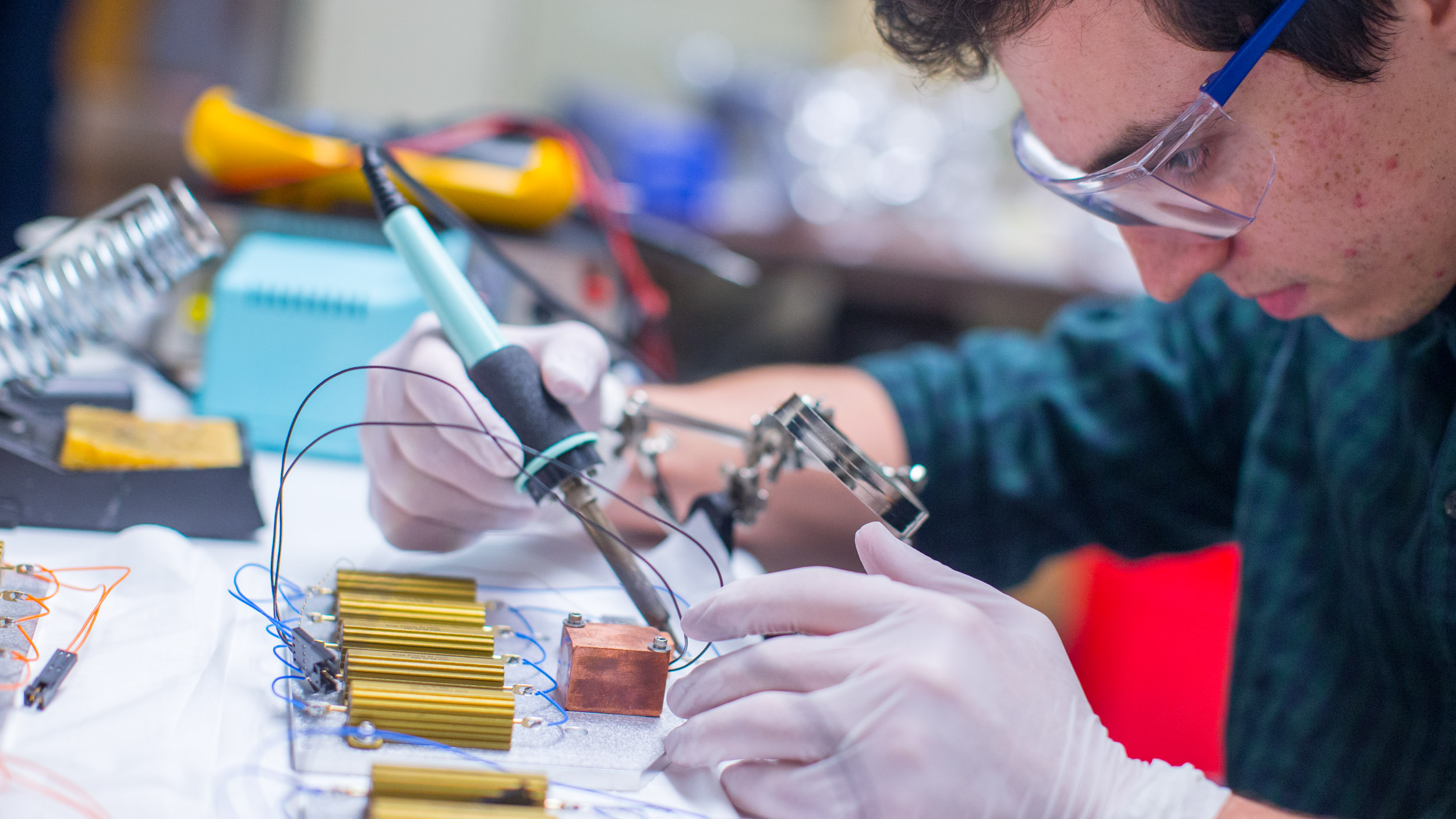 Recent UVA graduate and now lab technician Matthew Hall assembles electronic circuitry for APOGEE's thermal warm-up system.