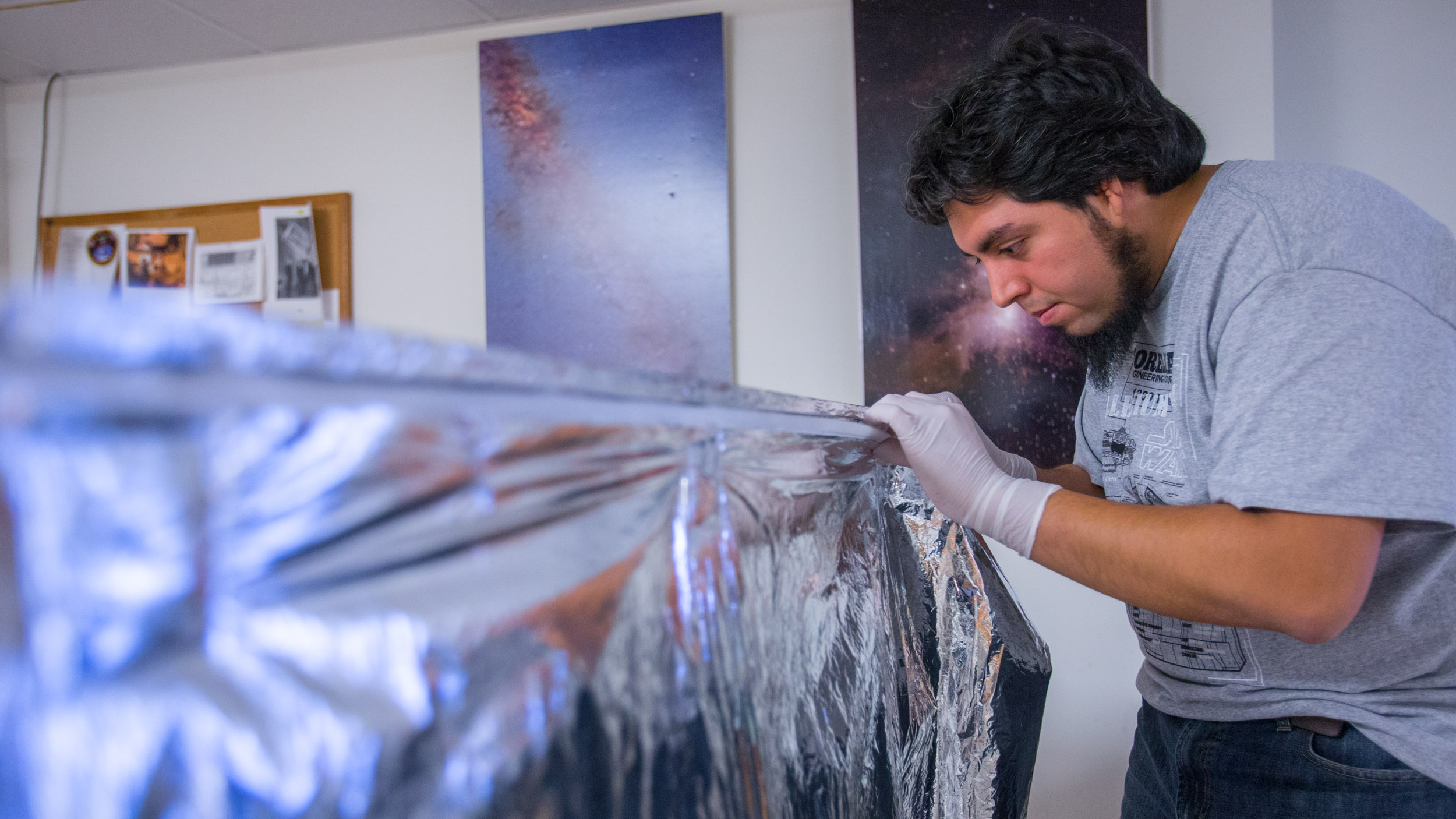 Visiting Chilean graduate student Juan Pablo Colque Saavedra of the University of Antofagasta test-fits special thermal radiation blankets to a mock-up of the APOGEE instrument radiation shield.