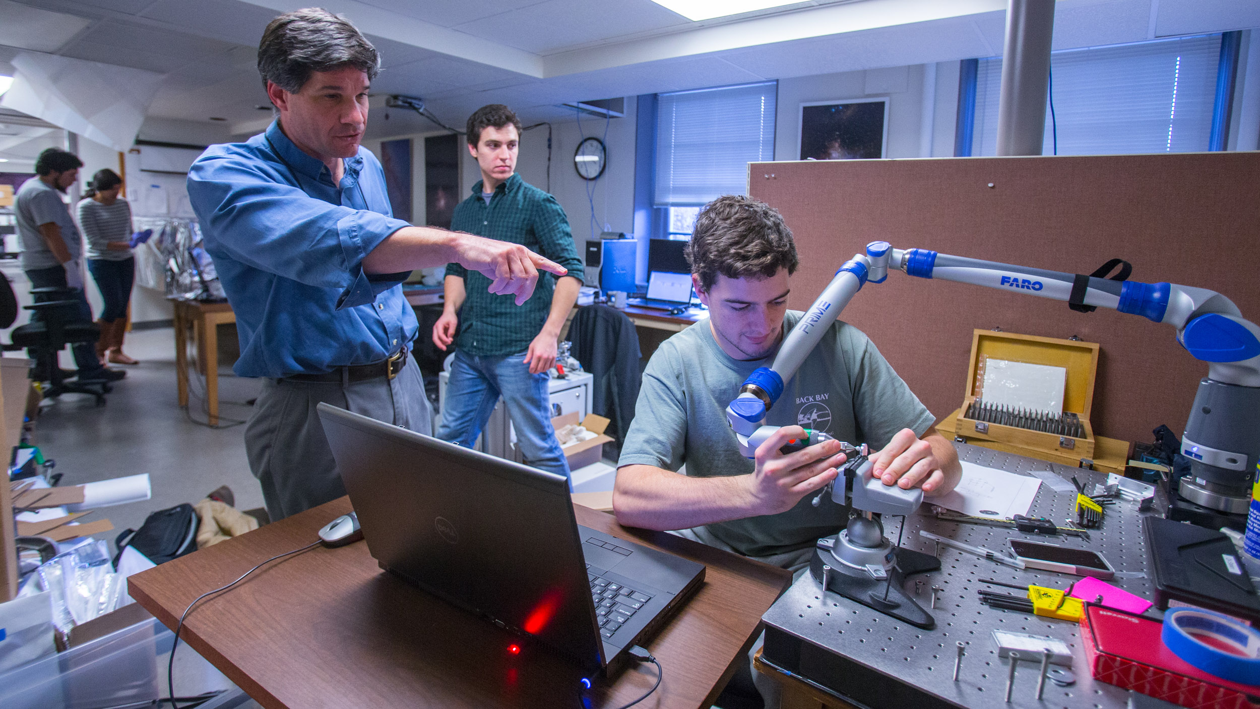 Senior scientist John Wilson directs student Brady Anthony-Brumfield in measuring a part milled in the astronomy machine shop.
