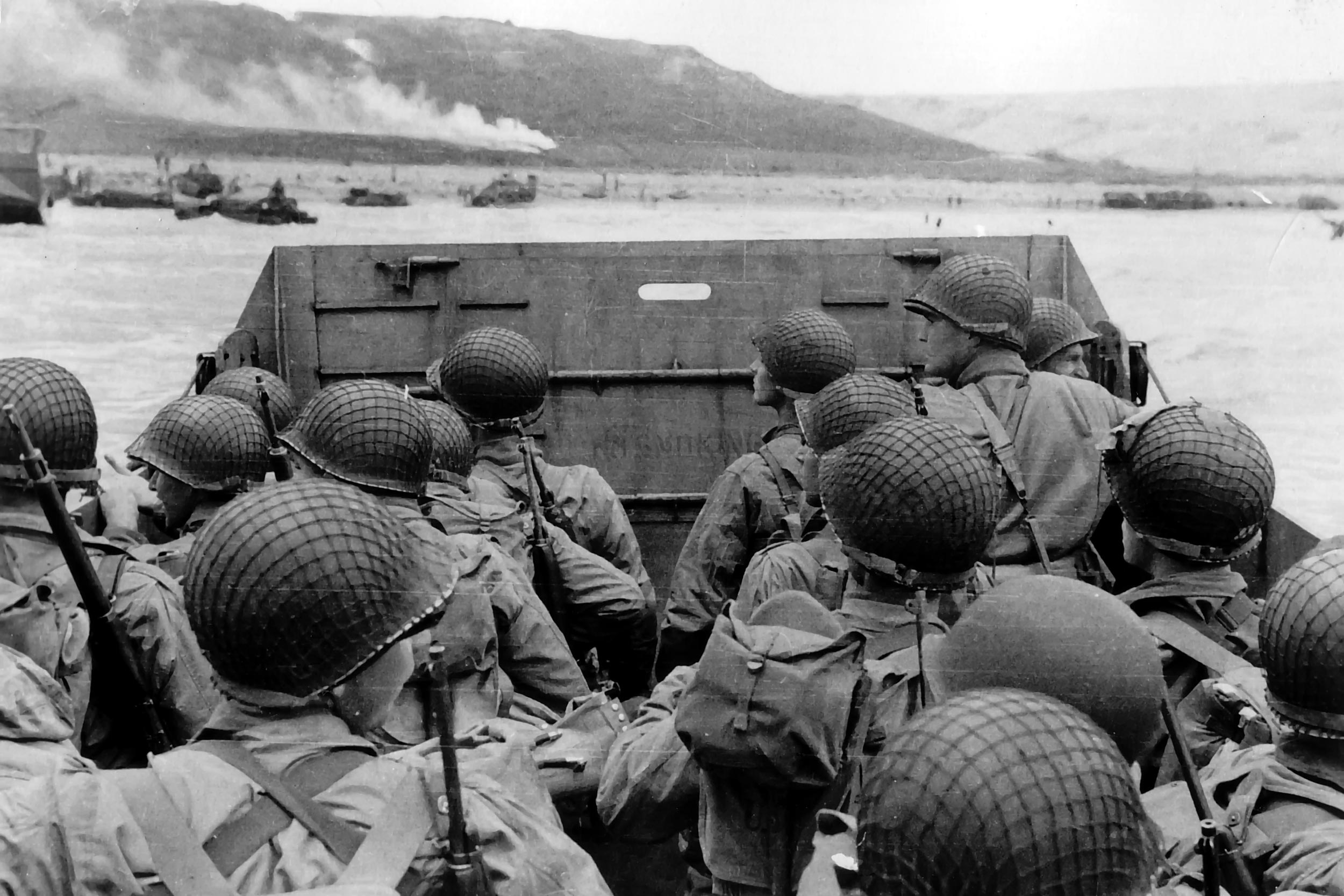 "Troops in an LCVP landing craft approaching ""Omaha"" Beach on D-Day. Note helmet netting; faint ""No Smoking"" sign on the LCVP's ramp; and M1903 rifles and M1 carbines carried by some of these men."