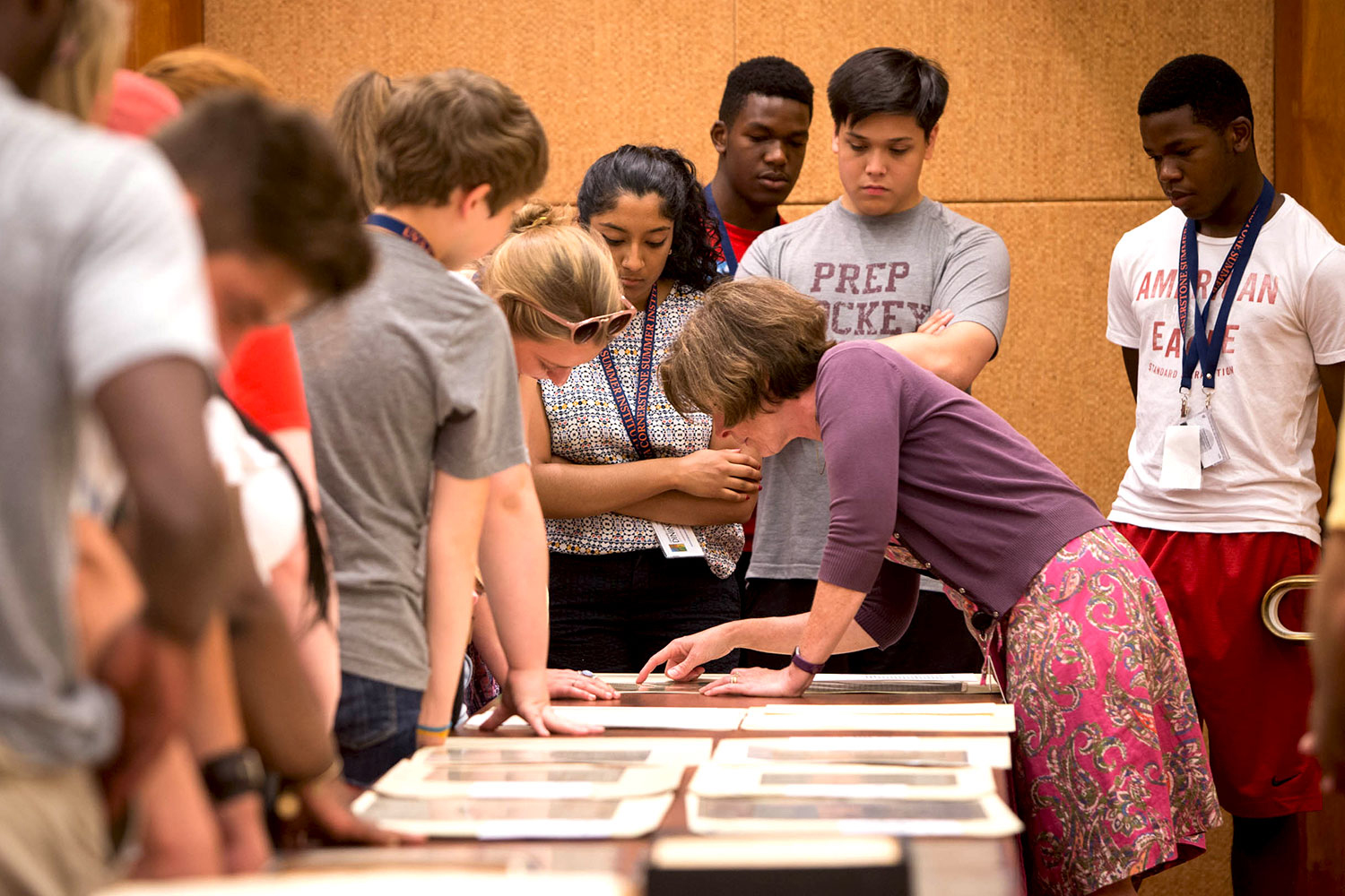 Heather Moore Riser, leaning down, head of public services in the Small Special Collections Library, shows high school students a selection of Thomas Jefferson's papers. (Photo by Sanjay Suchak/University Communications)
