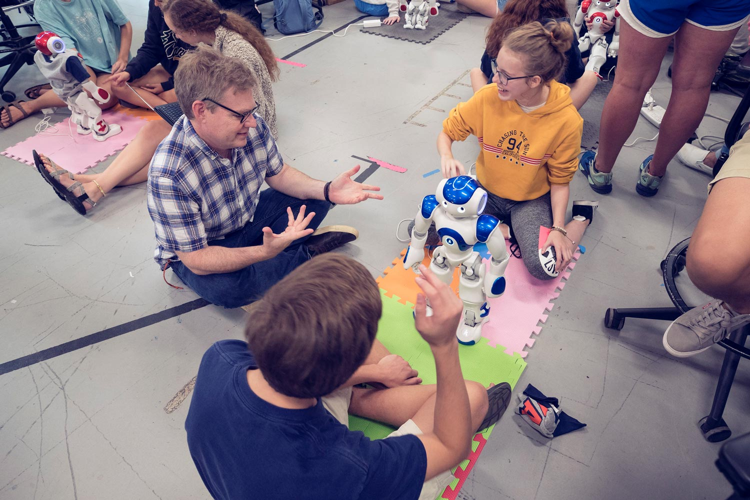 Engineering professor Keith Williams, left, works with students on programming their robot to follow commands.