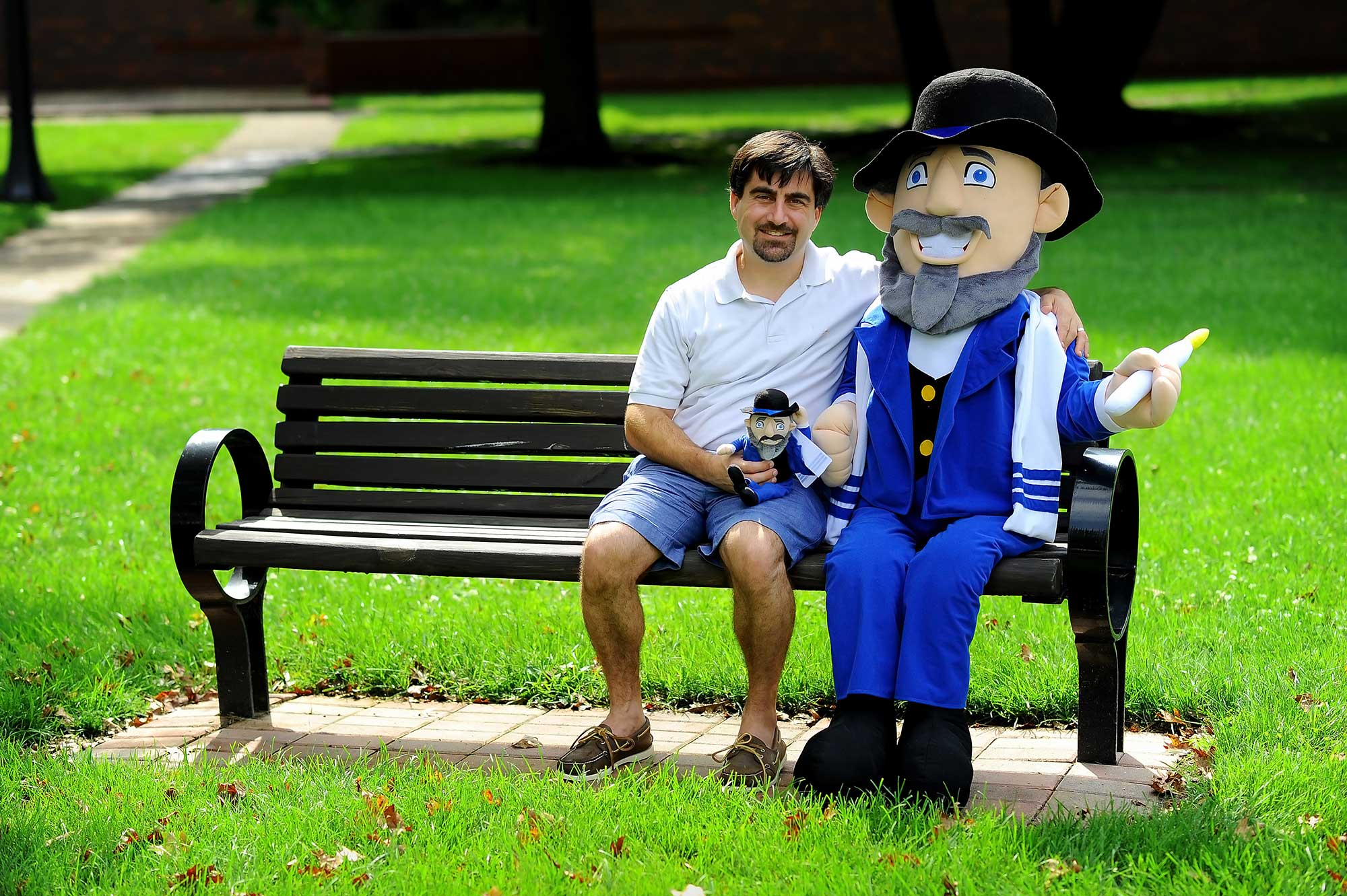 Neal Hoffman holds his Mensch on a Bench toy alongside a life-sized version.