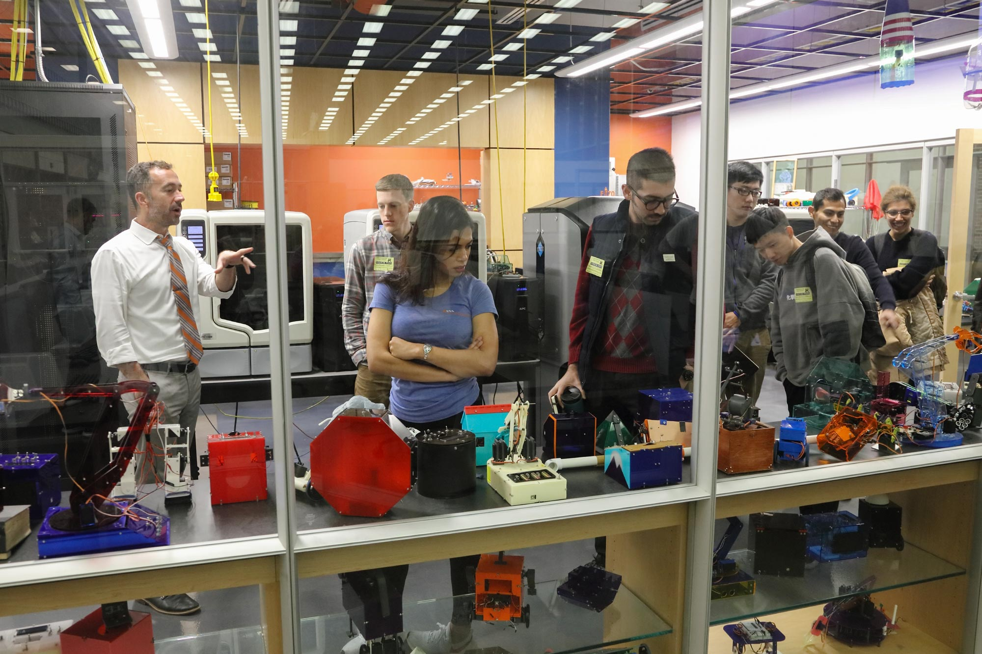 Matthew Shields, left, gives graduate engineering students (from left) Benjamin Bowes, Natalie Lerma, Arash Tavakoli, Ruijie Zhu, Wenqiang Chen, Luis Lopez Ruiz and Sonia Baee a tour of Charlottesville High's Sigma Lab.