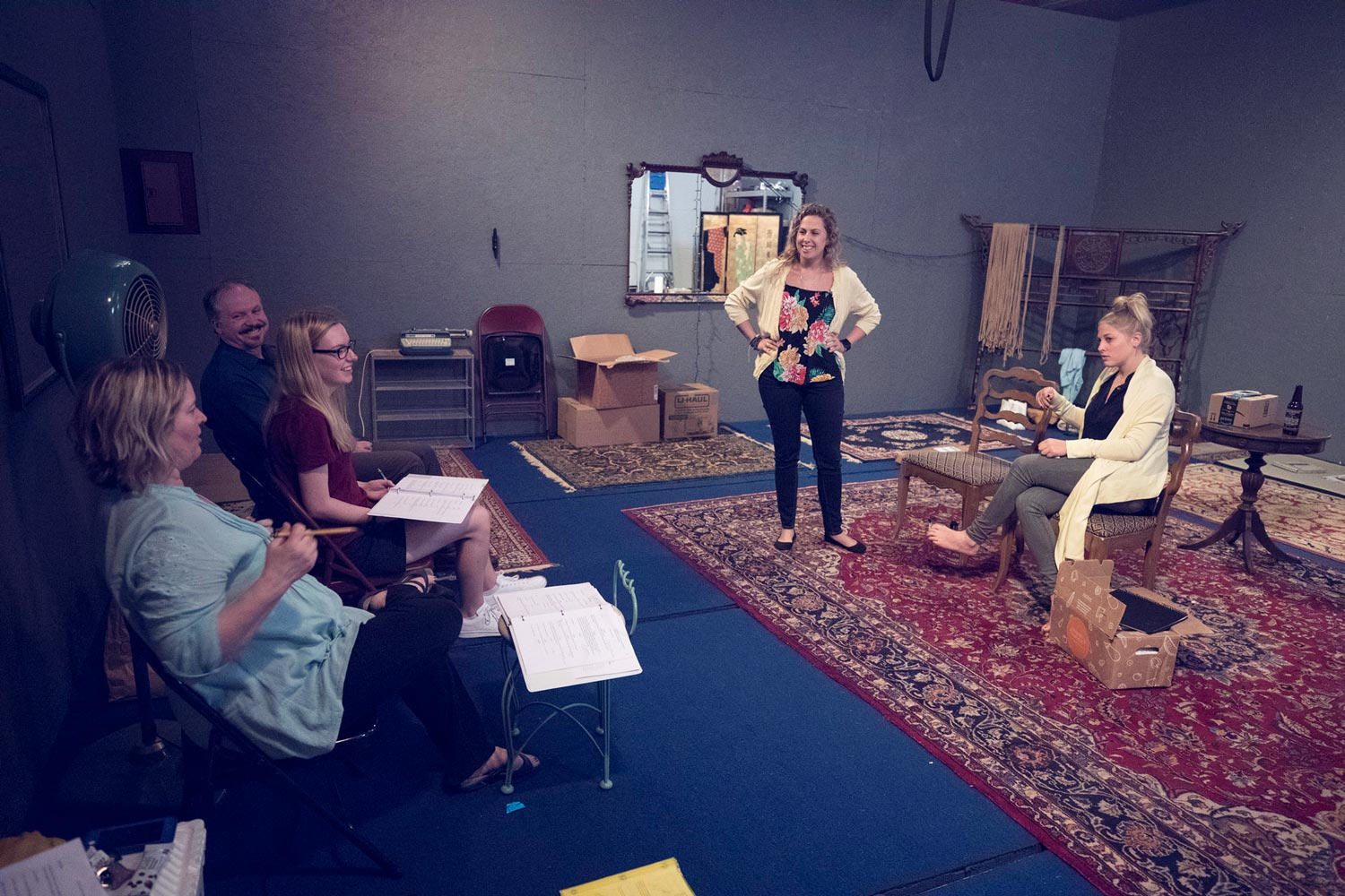 """Sean Michael McCord, far left, at a rehearsal of his play, """"Moving,"""" with director Joncey Boggs, left; Maeve Hickey, stage manager; Shannon Nara, standing, who plays """"Laura""""; and Kelsey Boggs as """"Robin."""""""