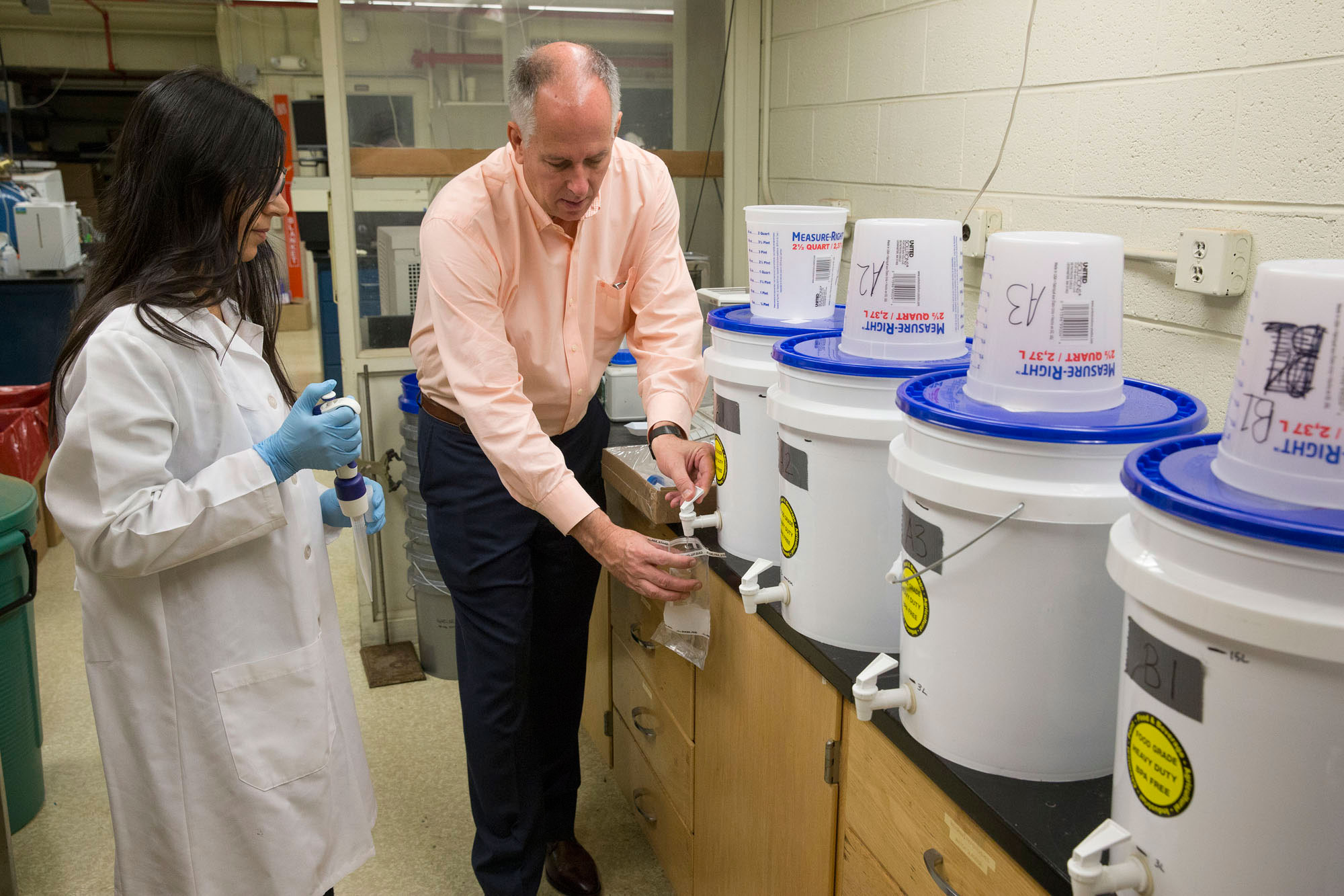James Smith and Rekha Singh, a research scientist in Smith's lab, demonstrate use of the MadiDrop tablet.