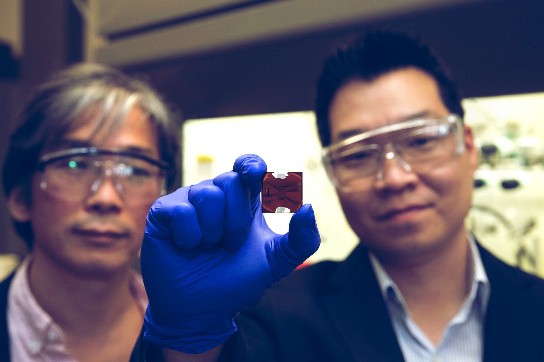 Physicist Seung-Hun Lee and chemical engineer Joshua J. Choi show off an example of a hybrid organic-inorganic perovskites, or HOIP. (Photo by Dan Addison, University Communications)