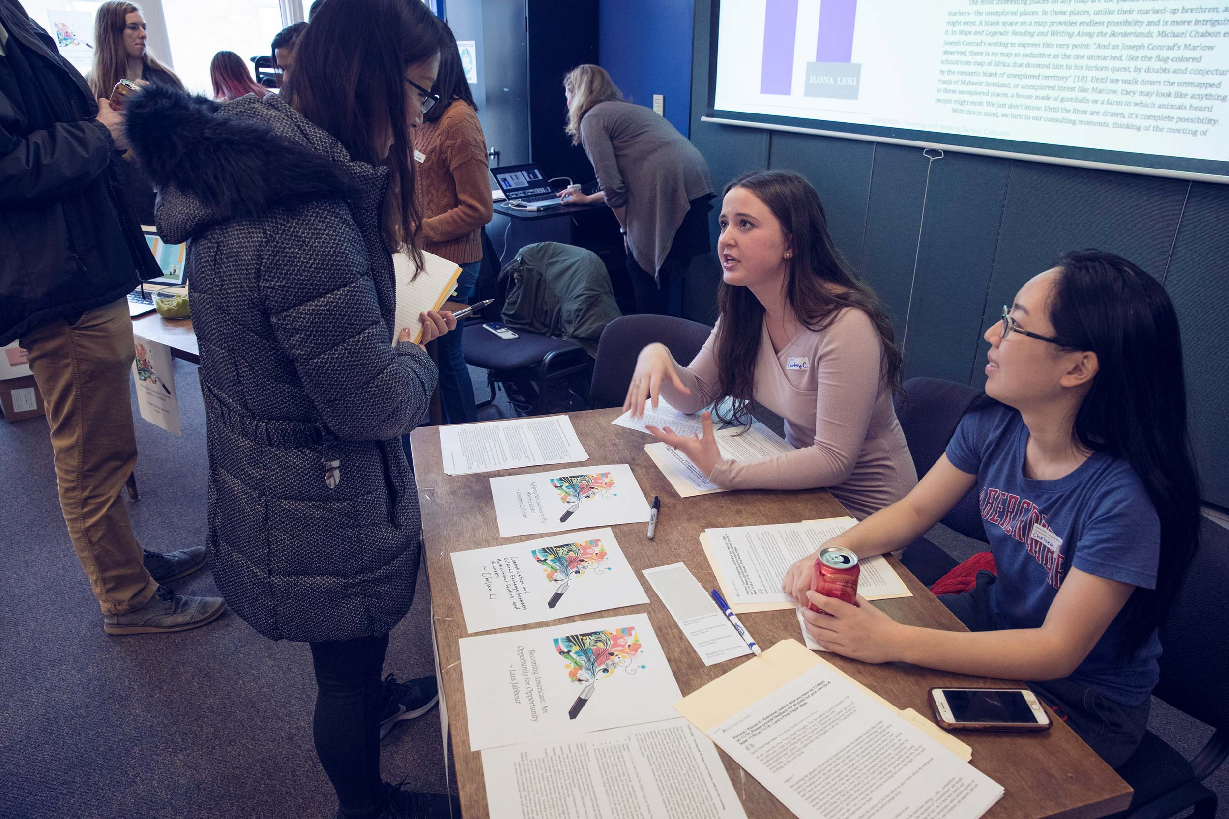 """Students Courtny Cushman, left, and Chelsea Li discussed their final projects for the course, """"Tutoring Writing Across Cultures,"""" at an English department showcase on community engagement."""
