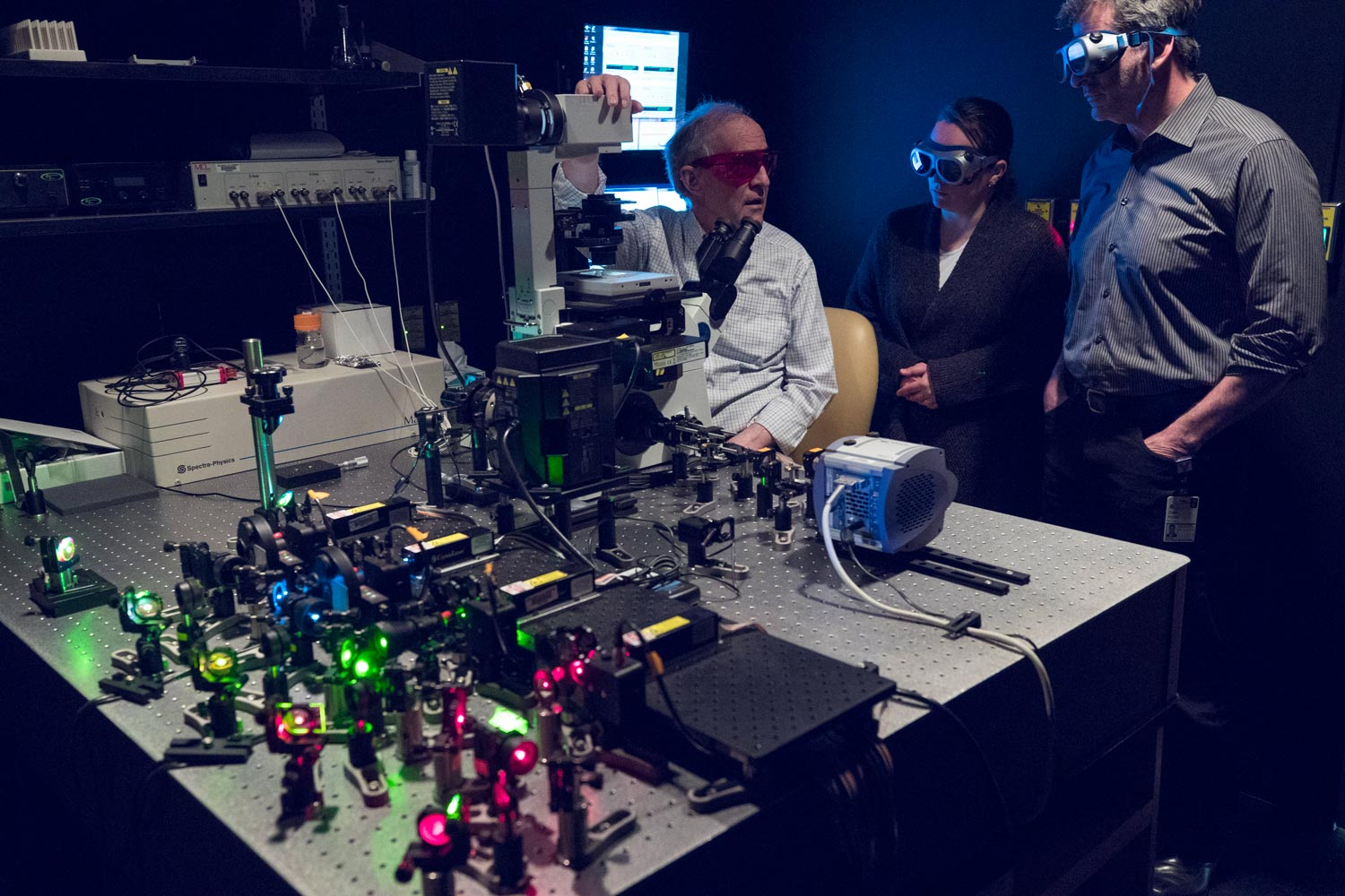 From left, researchers M. Mitchell Smith, Margaret J. Grant and Dean H. Kedes devised their own laser microscope to peer deeply into sub-cellular structures.