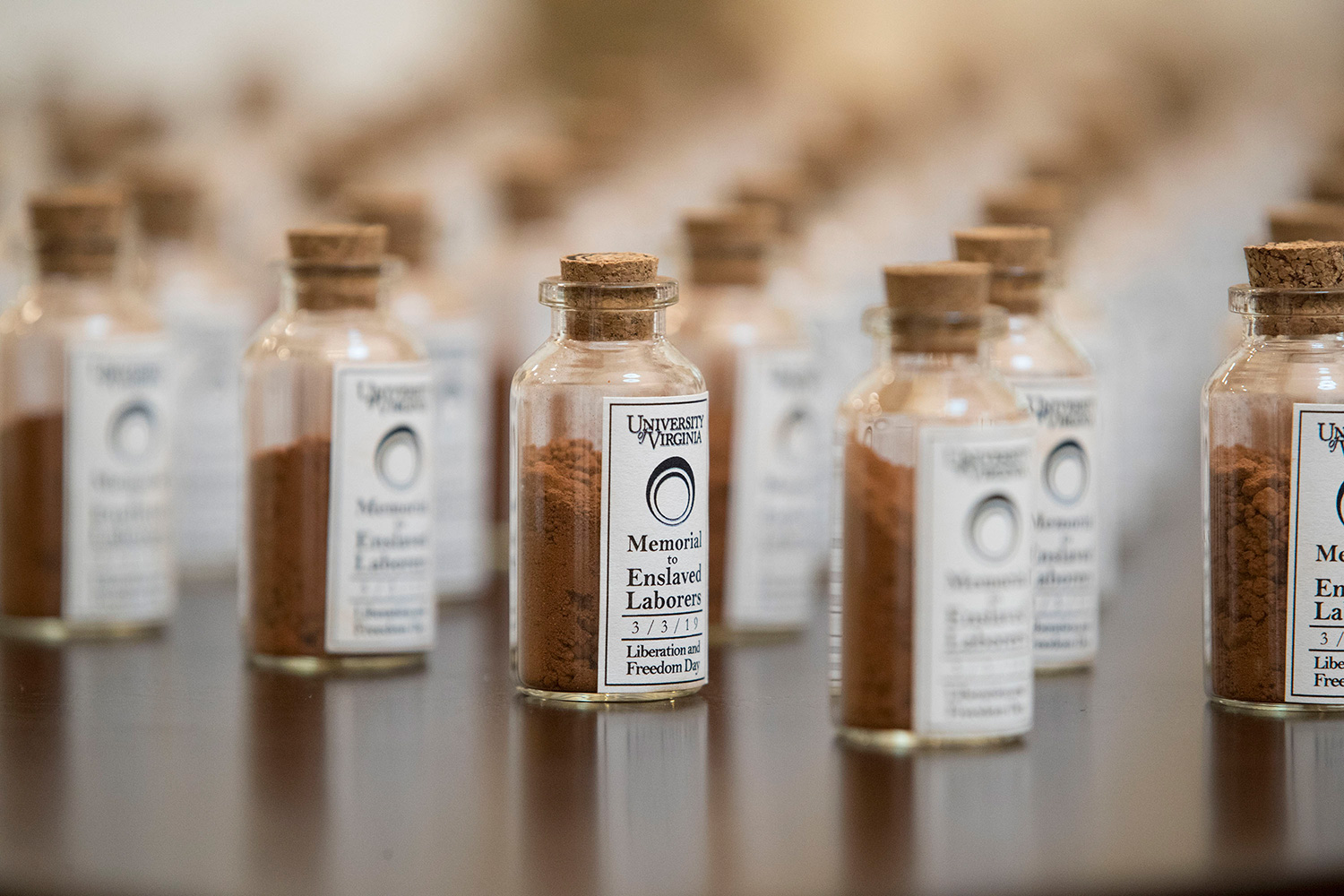Commemorative vials of soil from the memorial construction site were given away, the same kind of soil enslaved laborers might've used to make the bricks seen in the Academical Village.
