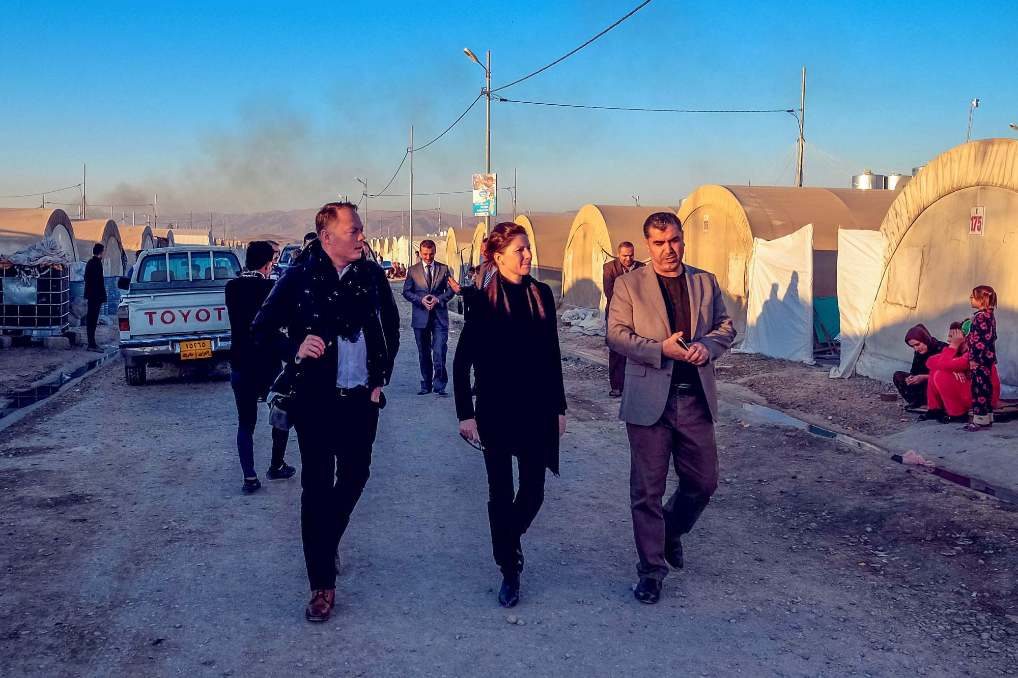 Alight Fund co-founders John Kluge, left, and Christine Mahoney walk with an interpreter while visiting a Syrian refugee camp in Iraqi Kurdistan.