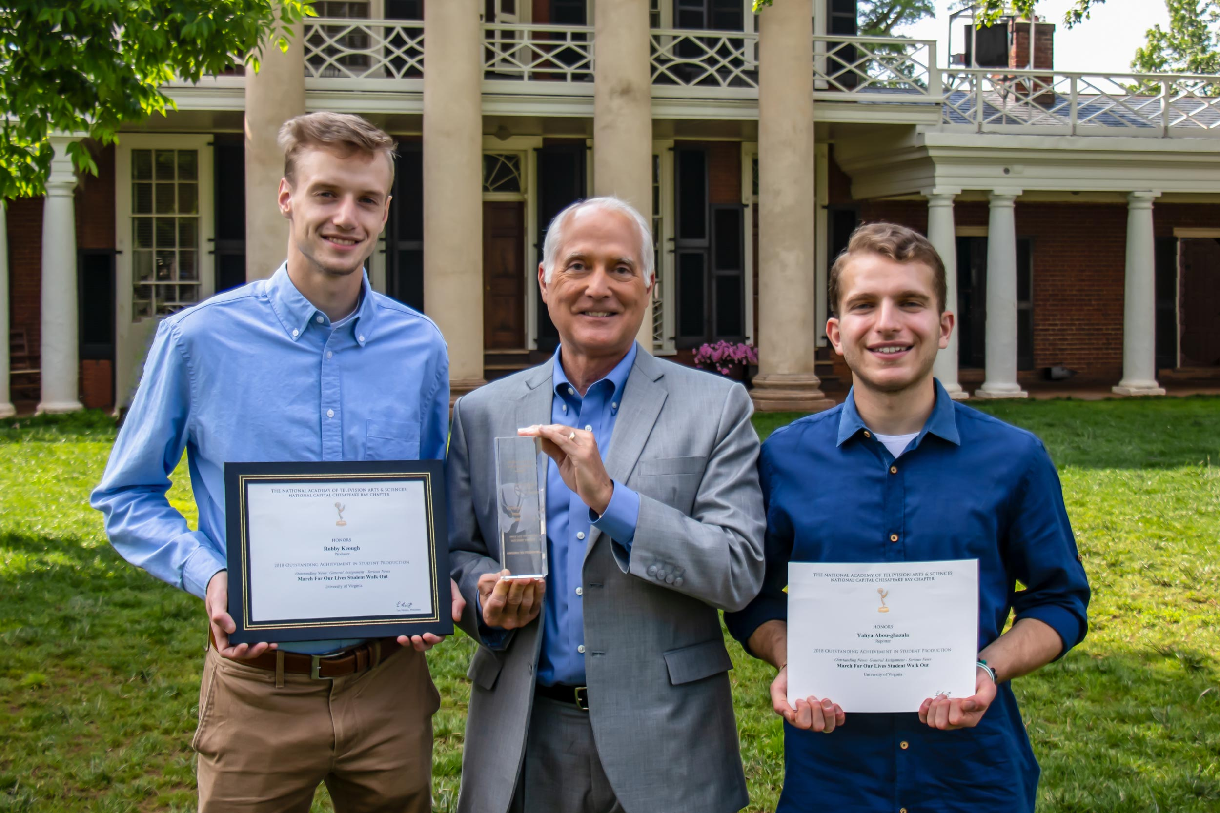 """From left, Robby Keogh, media studies professor (and former CBS News correspondent) Wyatt Andrews and Yahya Abou-Ghazala celebrate the students' Emmy for coverage of the """"March for Our Lives"""" rally at UVA."""