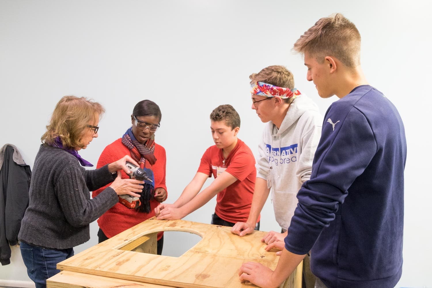 """Student Chris Sausa, right, and his """"little brother"""" Johan, center, along with student Garrett Lukens, build doghouses with Sharon Shafer from Houses of Wood and Straw, left, and NBC-29 reporter Moriah Davis."""