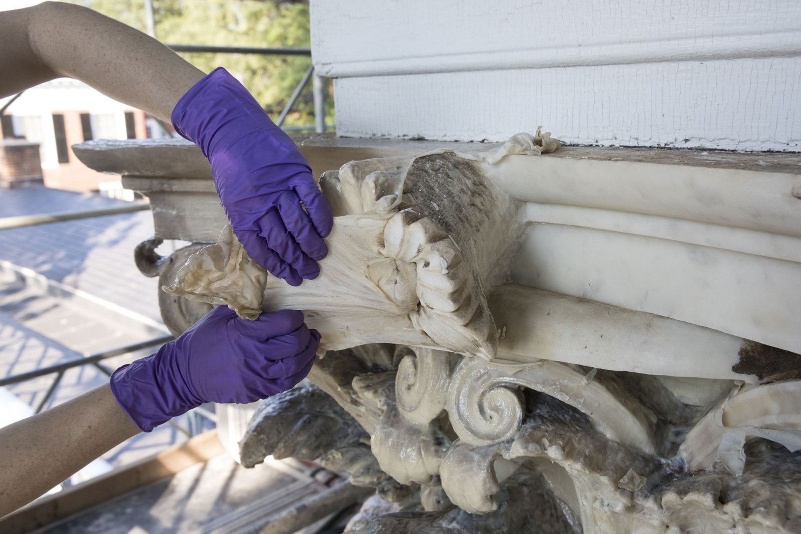 """Leigh Hassler cleans one of the marble capitals at Pavilion III. """"It certainly feels more personal than my other jobs,"""" she said. """"I feel a little sense of ownership."""" (Photo by Dan Addison/University Communications)"""