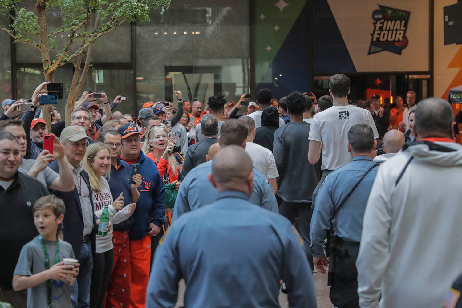 The Cavalier basketball team makes their way through the hotel atrium Monday afternoon, to the delight of hundreds of fans.