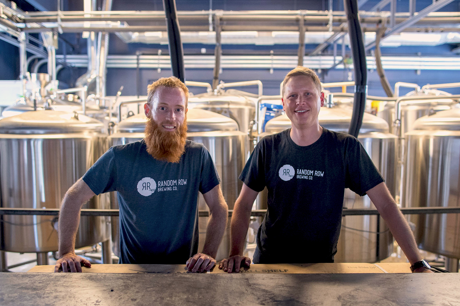 Kevin McElroy, left, and Bradley Kipp stand behind the bar at Random Row Brewing Co. (Photo by Sanjay Suchak/University Communications)