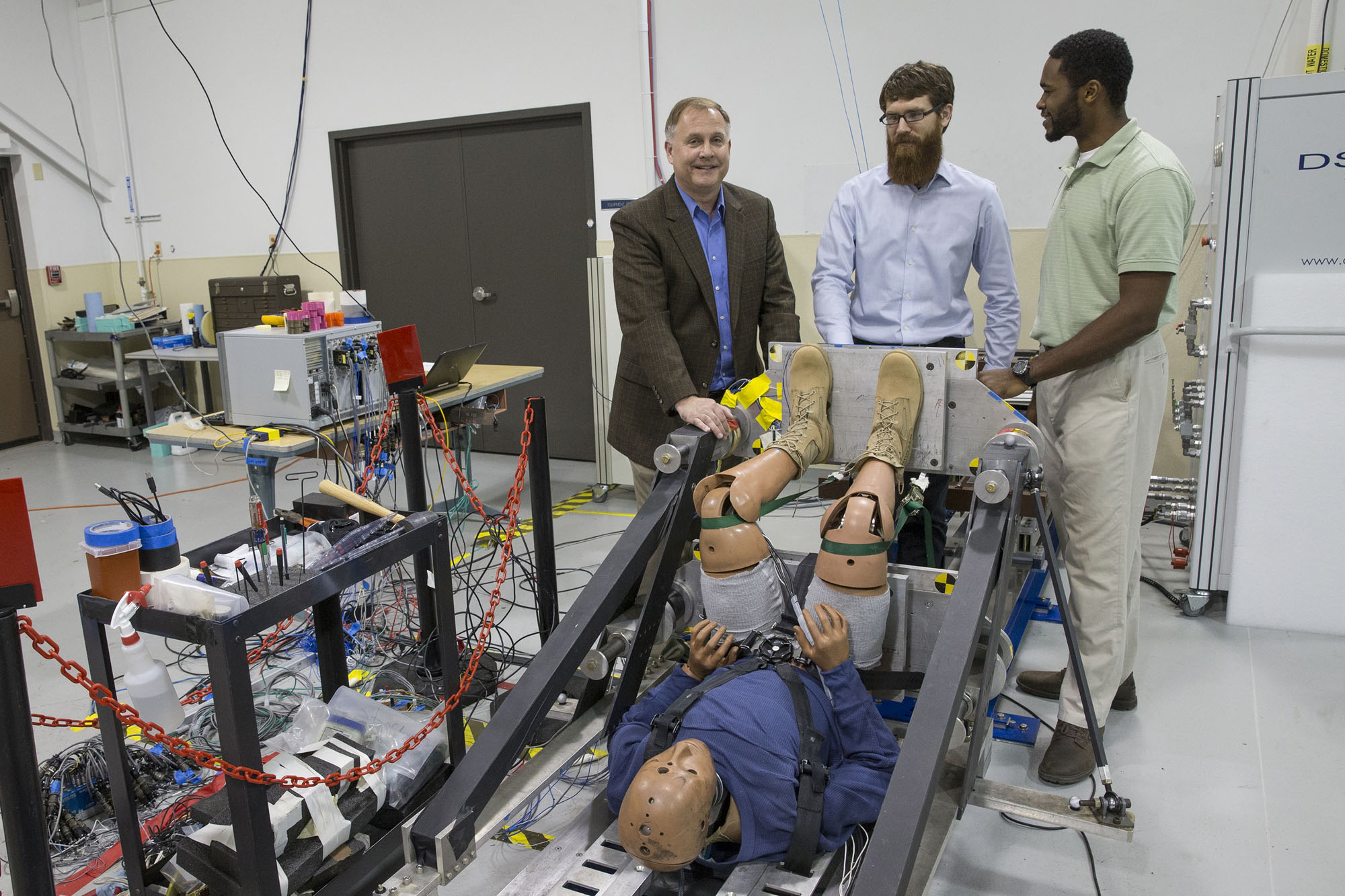 Robert Salzar, left, and his research team members, Aaron Alai, center, and Kyvory Henderson, right, discuss a device they designed for studying blast injuries.