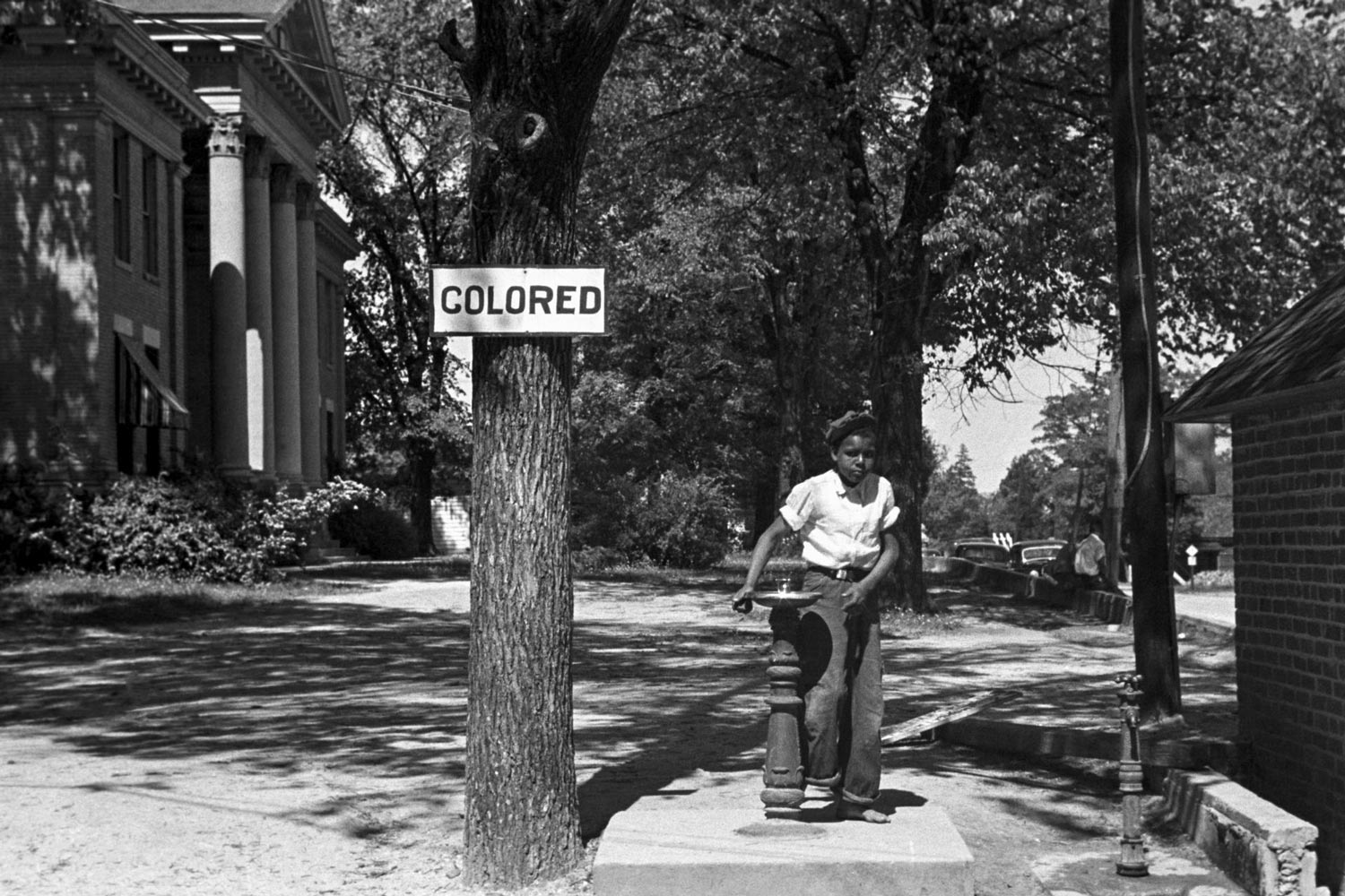A boy at a segregated drinking fountain on the county courthouse lawn in Halifax, North Carolina in April 1938.