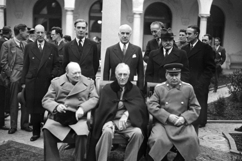 Secretary of State Edward R. Stettinius Jr. stands at center behind (from left) Winston Churchill, Franklin D. Roosevelt and Josef Stalin at the Yalta Conference.