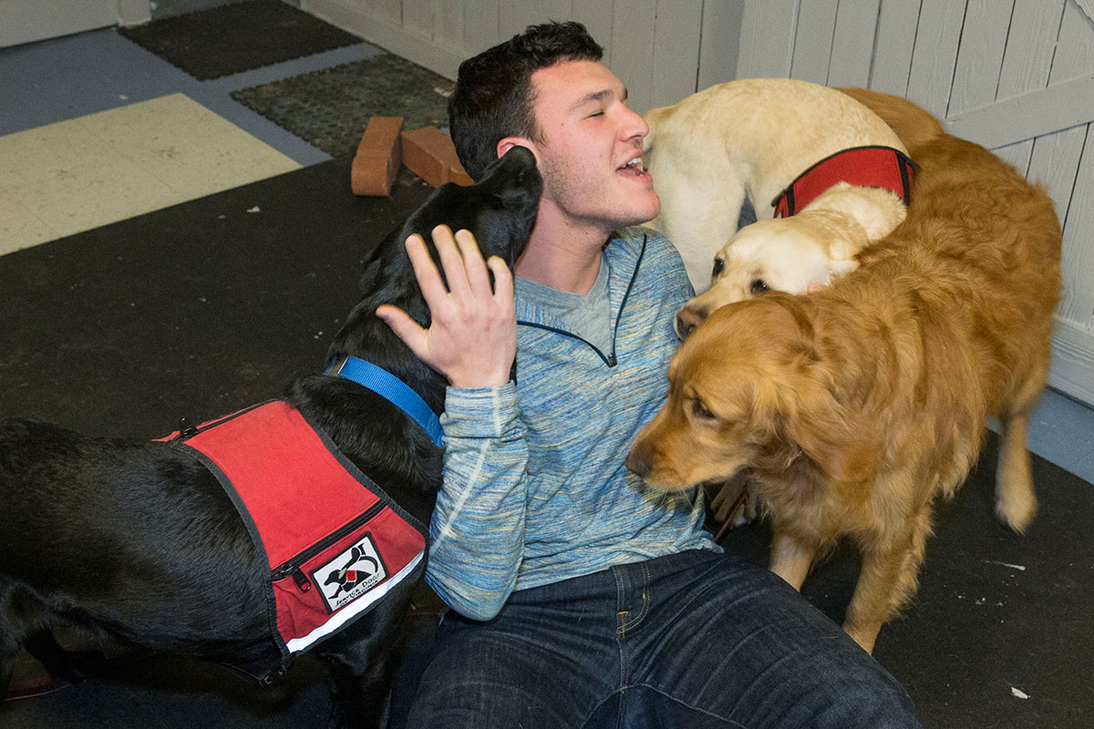 Totem co-founder Kyle Matthews meets some of the pups of Service Dogs of Virginia, the latest beneficiaries of the new app's fundraising model.
