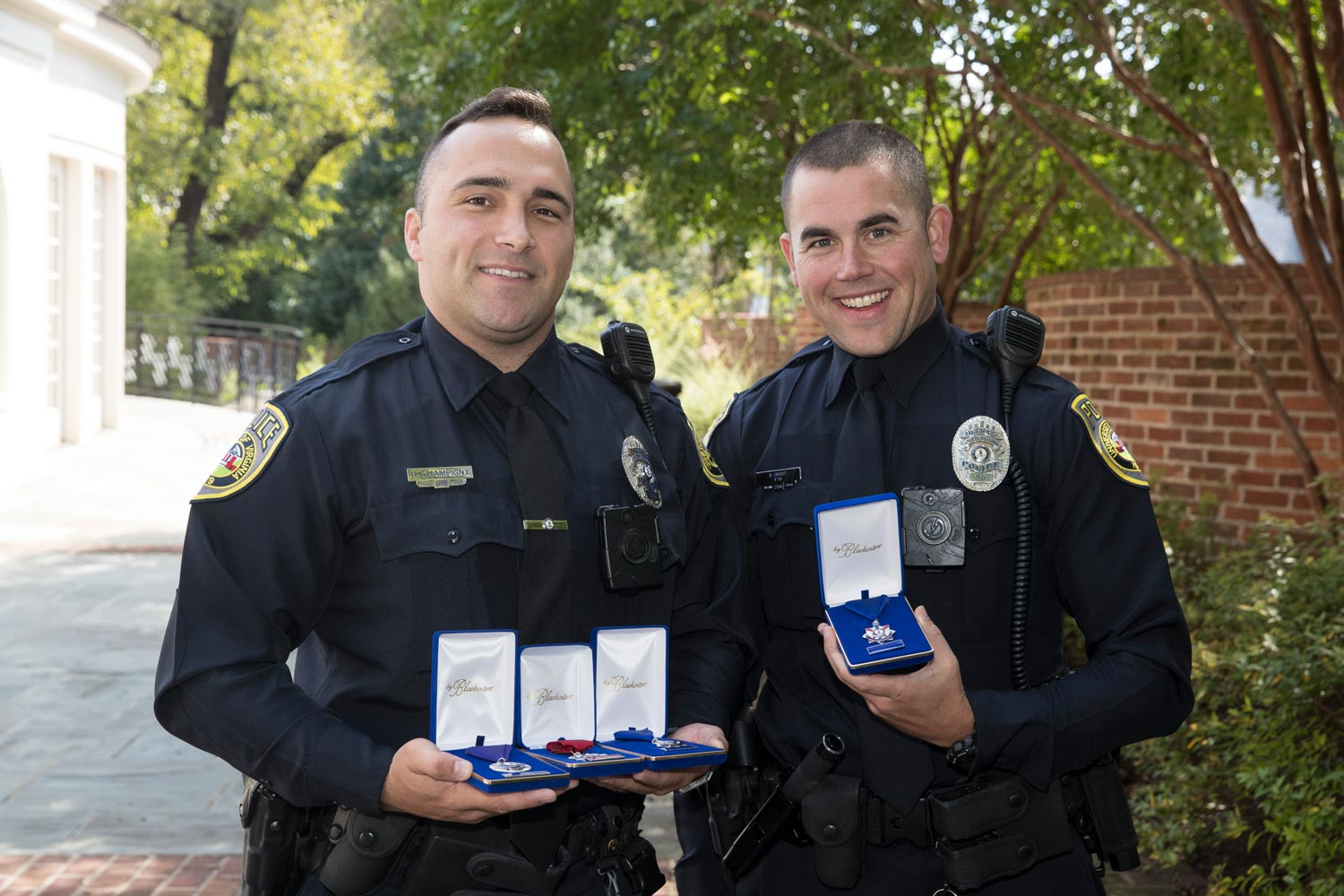 UVA Police Officers Nicholas Champigny and Brandon Smoot stand in a courtyard outside Alumni Hall, proudly holding their awards.