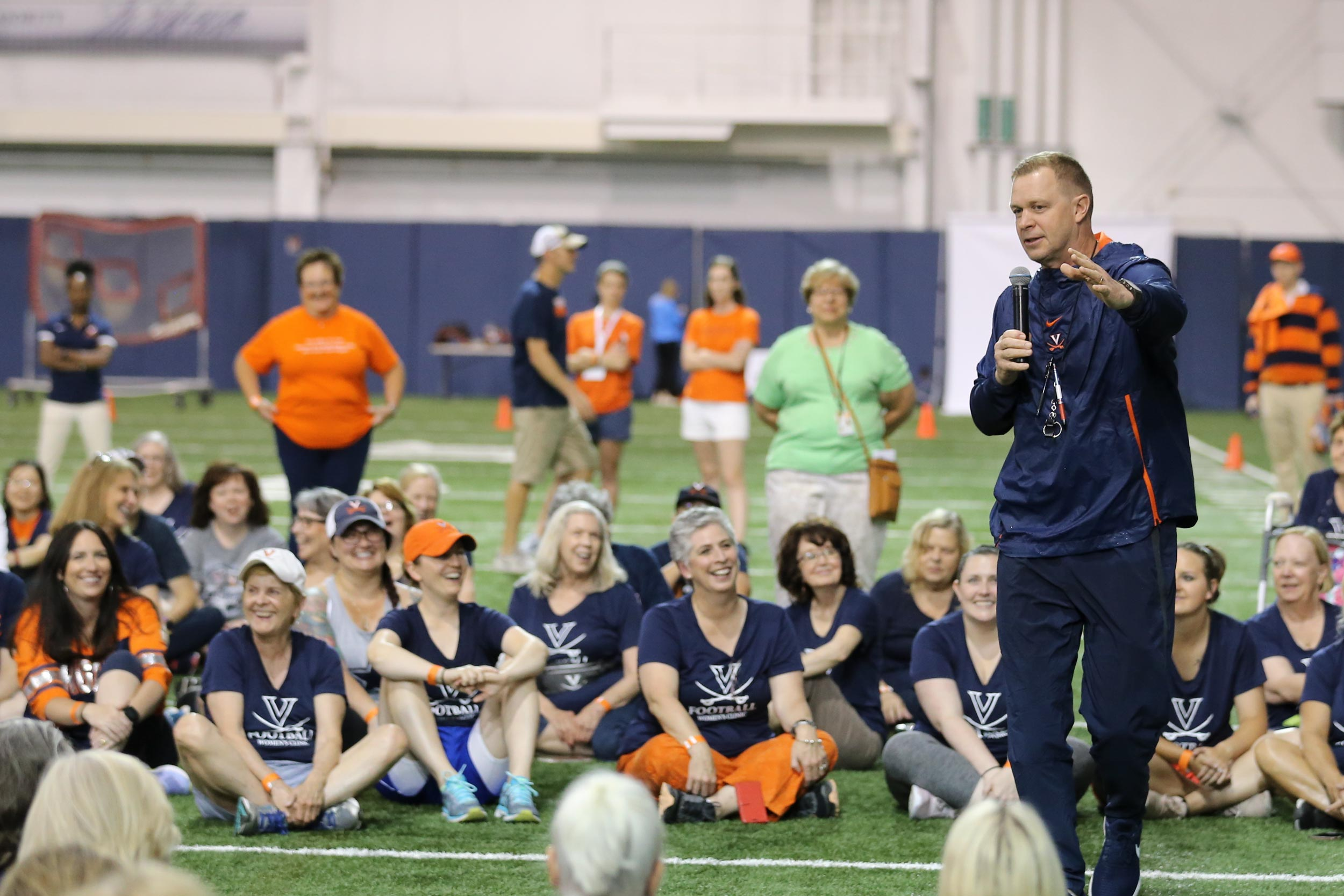 UVA football head coach Bronco Mendenhall chats with participants.