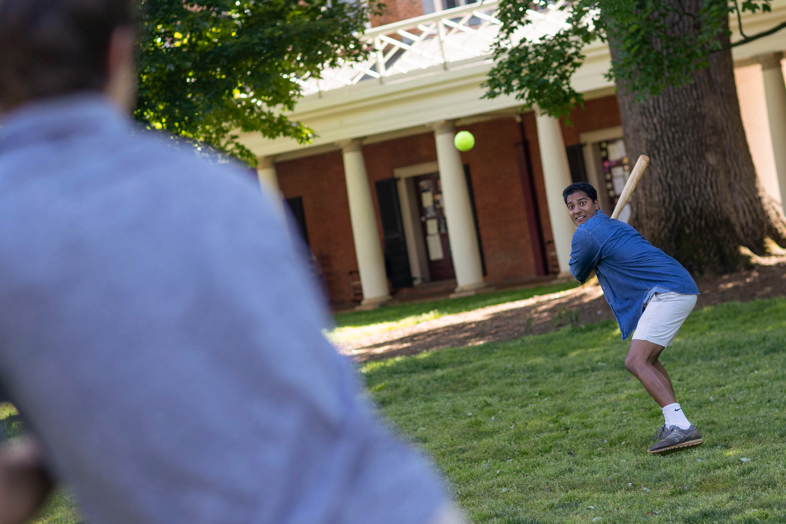 """Samuel takes a swing playing """"Peachball"""" on the Lawn. He doesn't know the origin of the name, but the game is similar to baseball. Players use pizza boxes and College Inn cheese bread boxes for bases."""