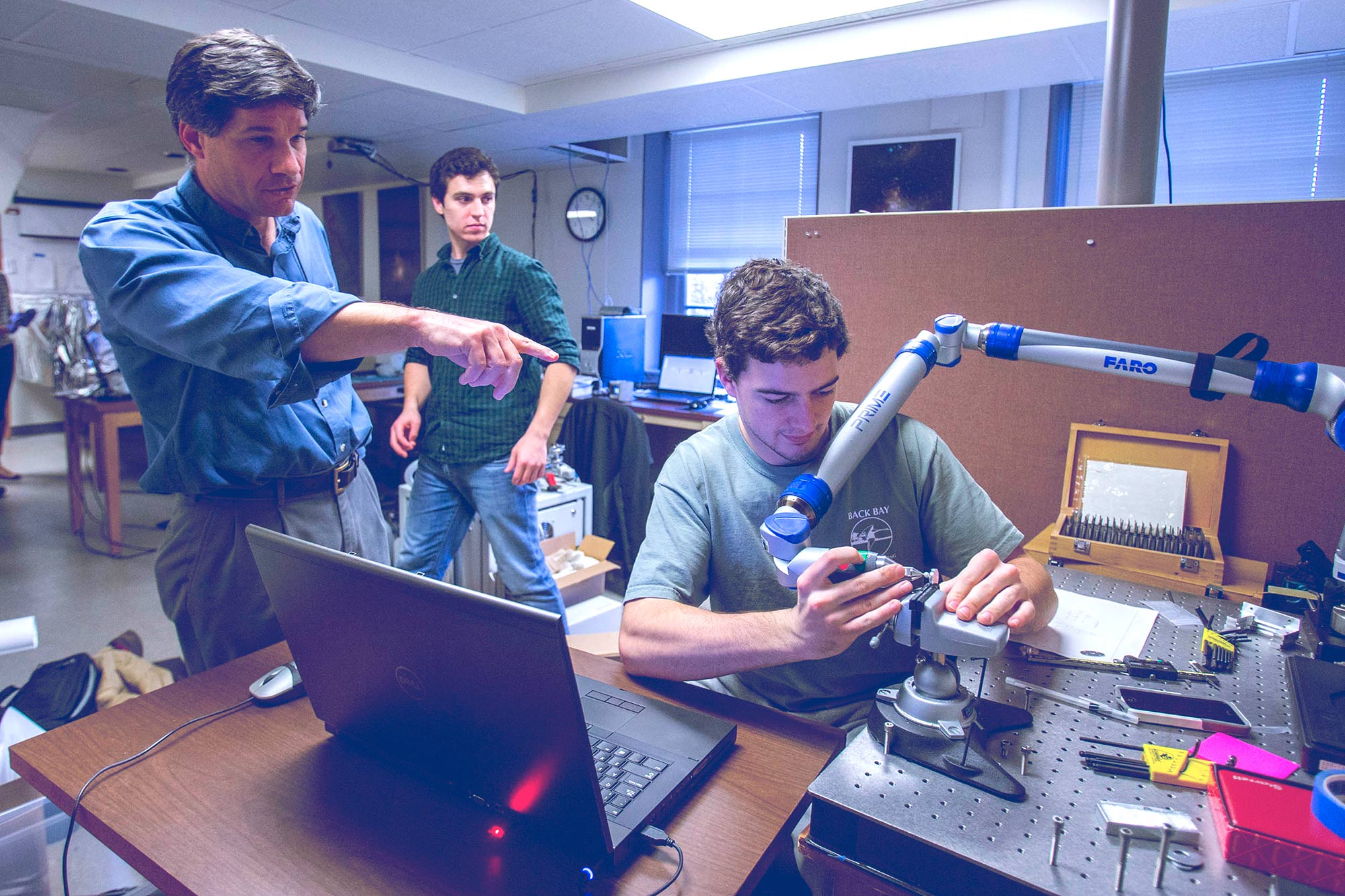 Instrument scientist John Wilson discusses a process with astronomy undergraduate Brady Anthony-Brumfield. Astronomy alumnus and lab technician Matt Hall, background, worked on APOGEE.