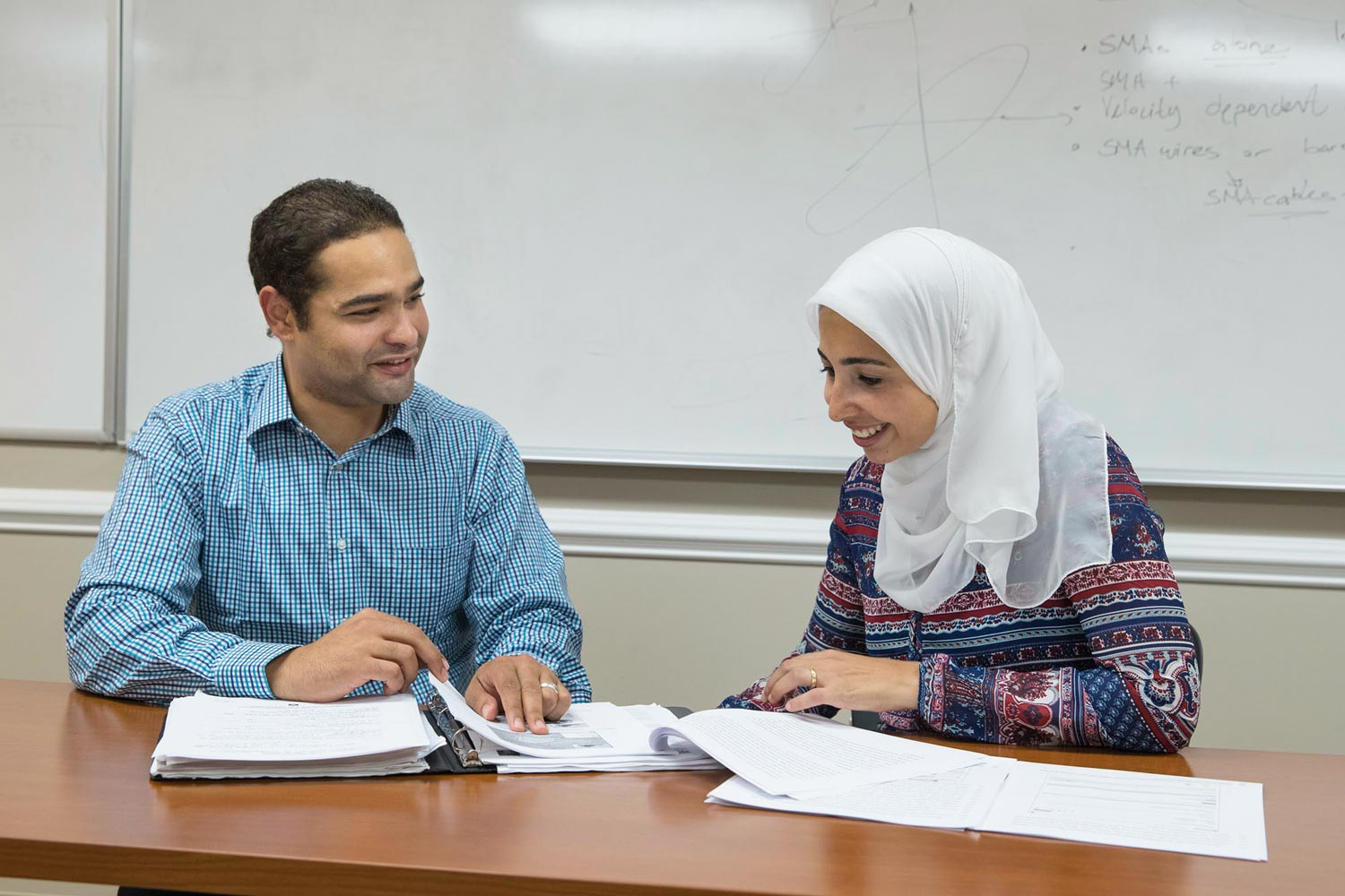 Mohamed Morsy and Bakinam Tarik Essawy compare hydrology reports after defending their dissertations.