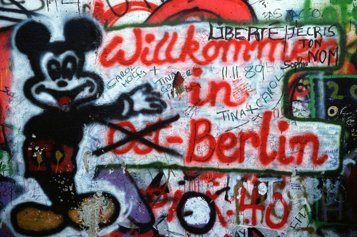 Graffiti on the west side of the Berlin Wall depicts the transition toward a unified Berlin in 1989.