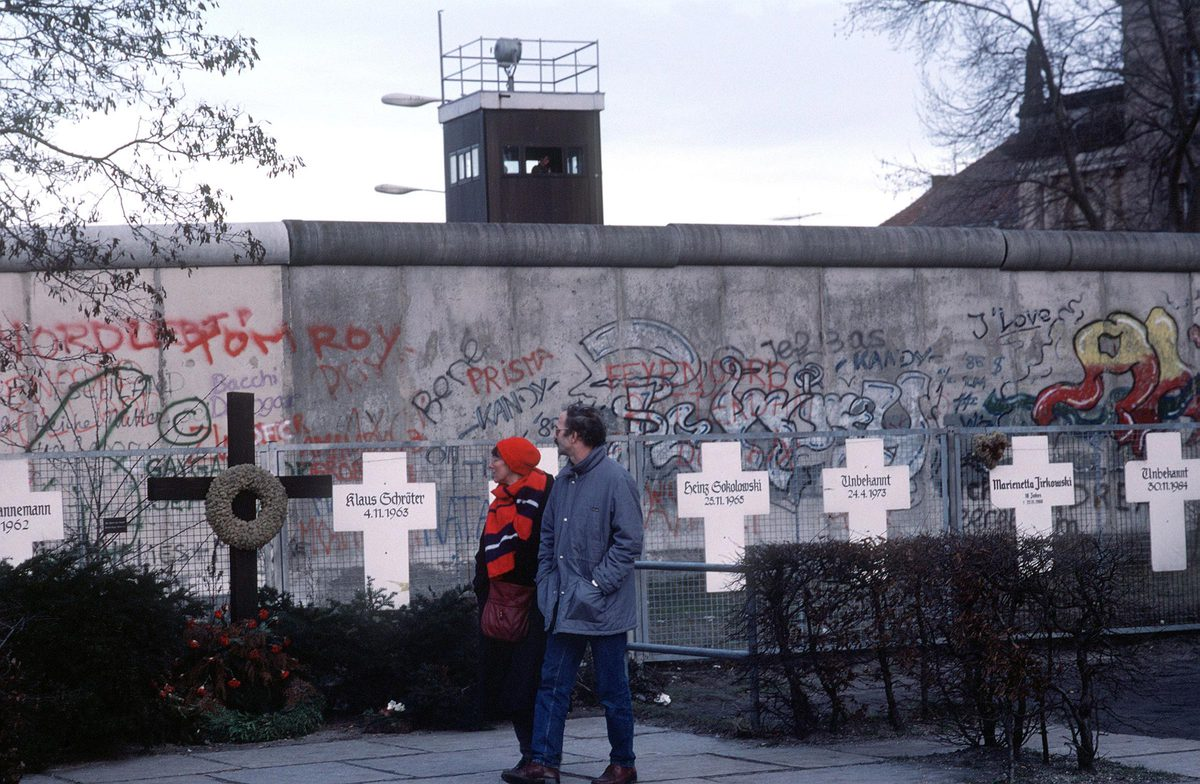 Following Germany's reunification, a couple reads grave markers of East Germans who died in an effort to escape over the Berlin Wall to the West.