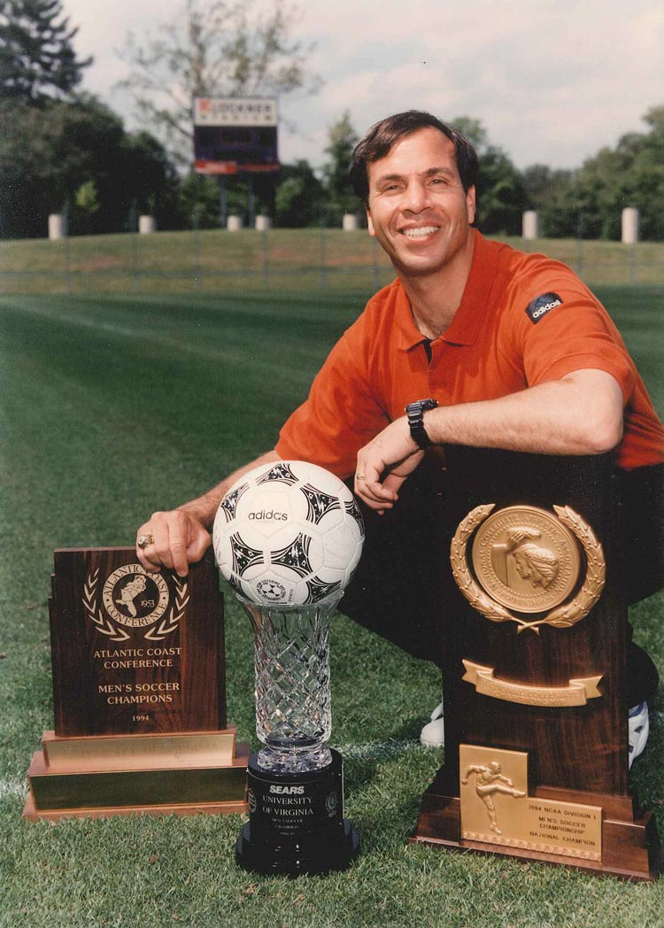 Bruce Arena with 1994 ACC trophy, Sears cup, and NCAA trophy for men's soccer