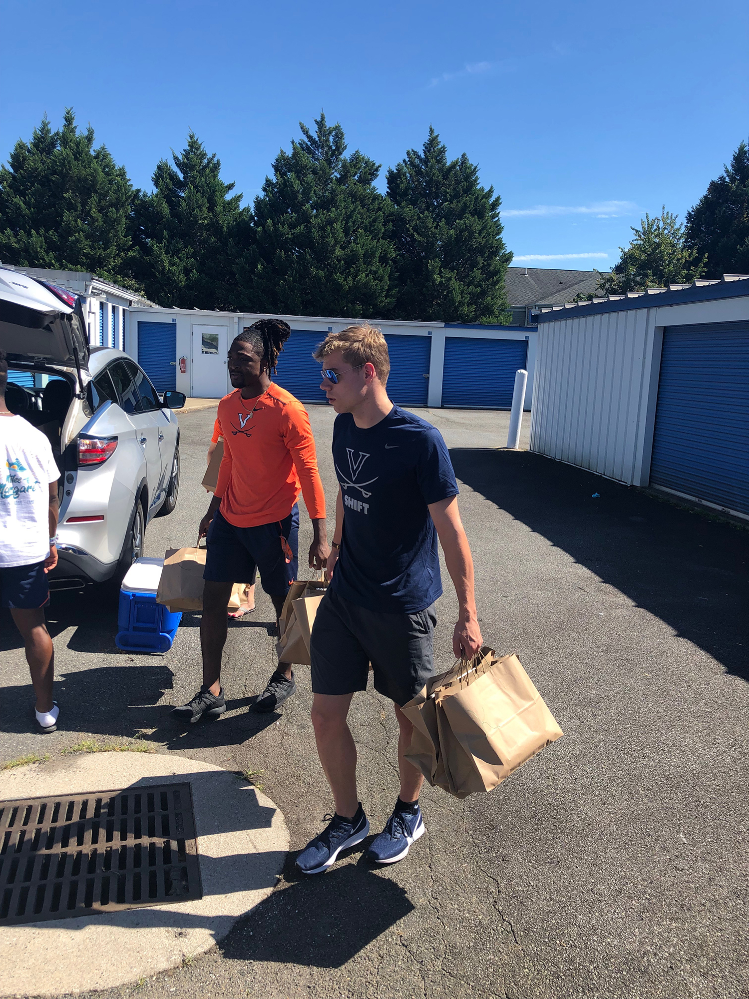 UVA quarterback Bryce Perkins, left, and swimmer Henry Schutte carry bags of books earmarked for kids into a storage unit. (Photo by Whitelaw Reid, University Communications)