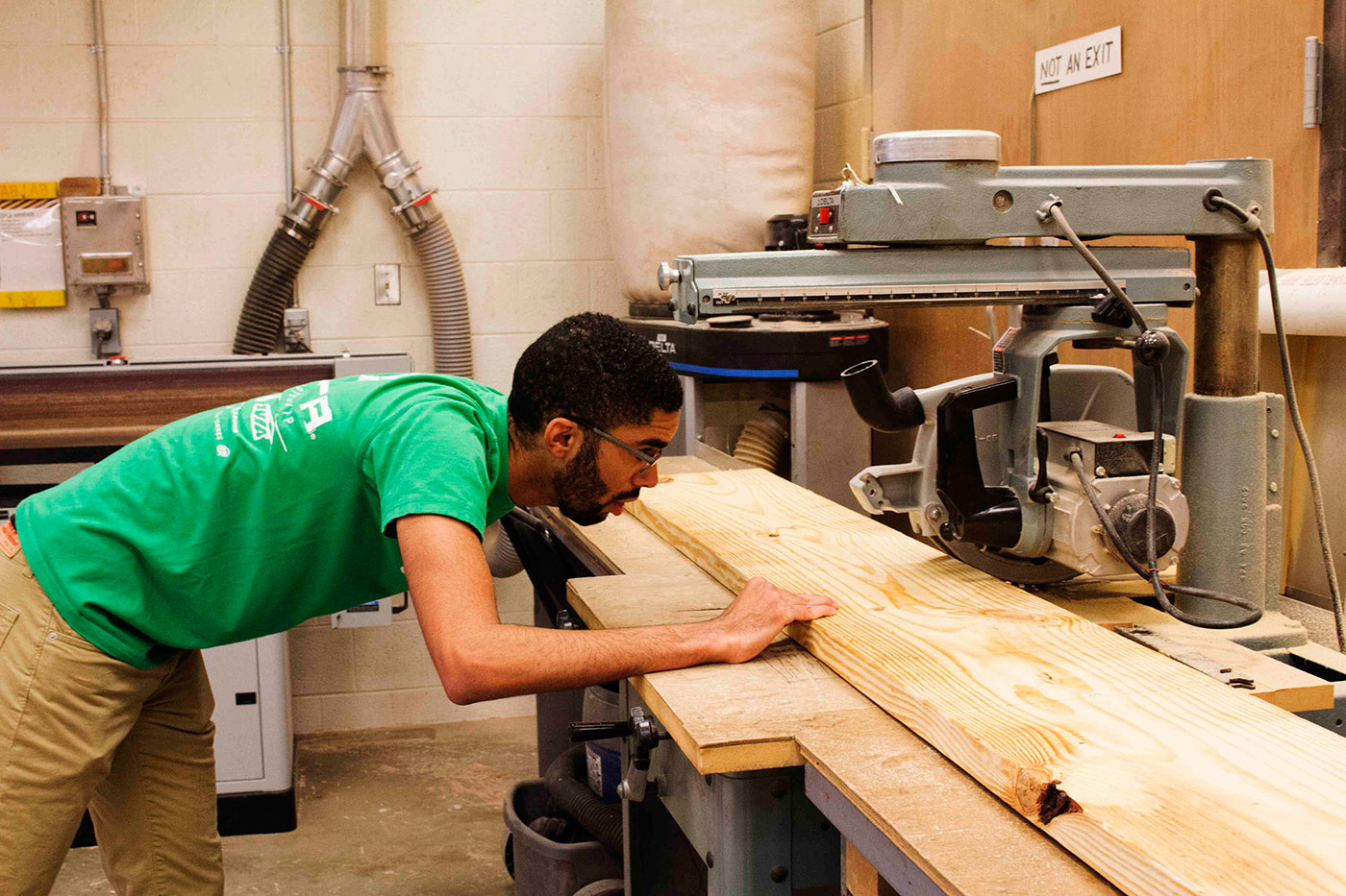 Third-year student Malik Vaughan, a volunteer with Growing for CHANGE, cuts wood for one of the garden boxes. Vaughan volunteered through the National Organization of Minority Architecture Students. (Photo courtesy of Shantell Bingham.)
