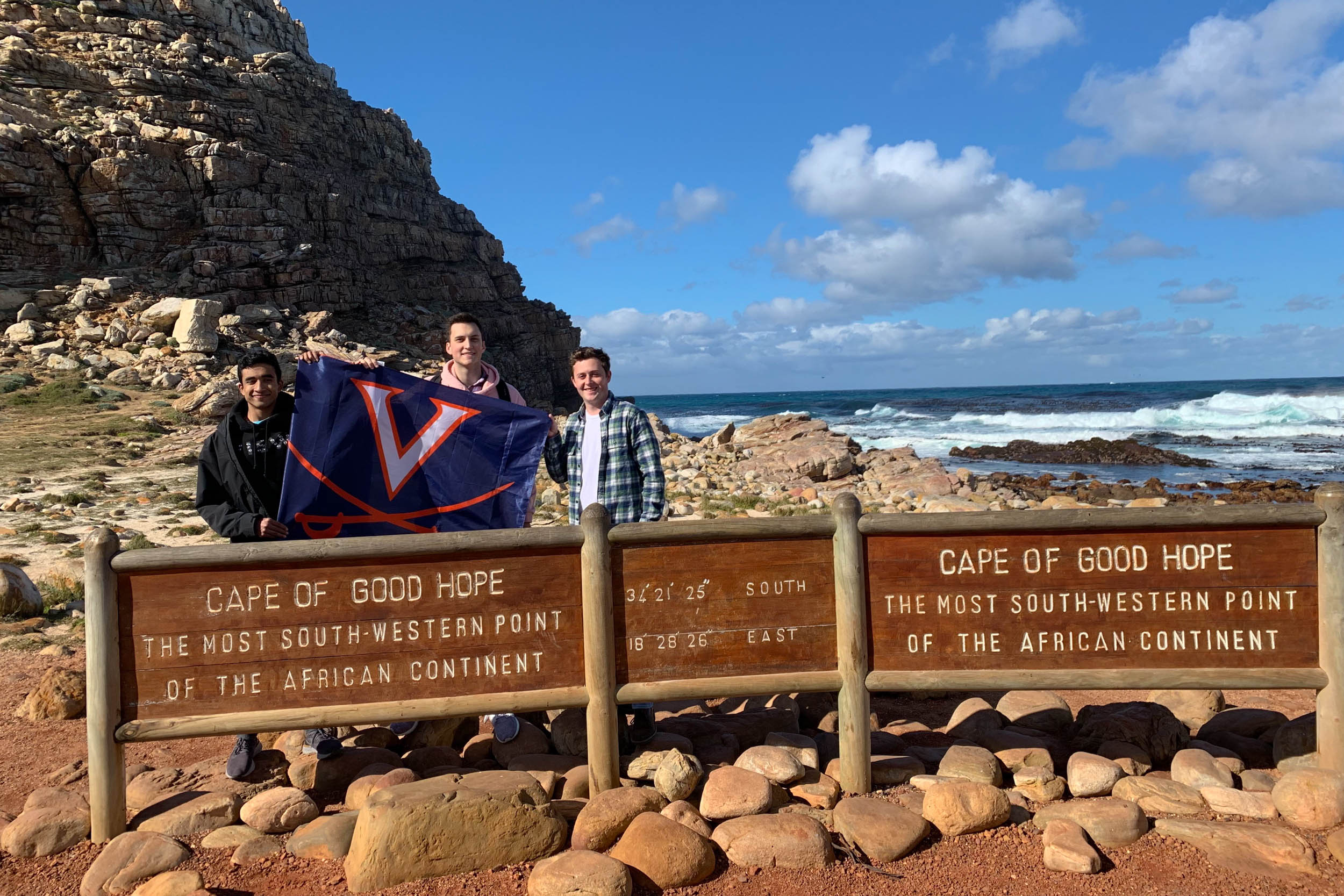 Left to right, Akash Bhat, Joel Thomas and Matt Ryan at the Cape of Good Hope showing their school spirit with a UVA flag.