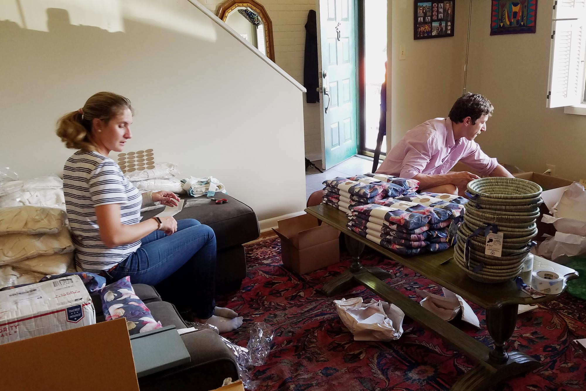 Marks' classmate, Katie White, left, and fiancé Gabe Legendy, right, help pack baskets ahead of Mother's Day.
