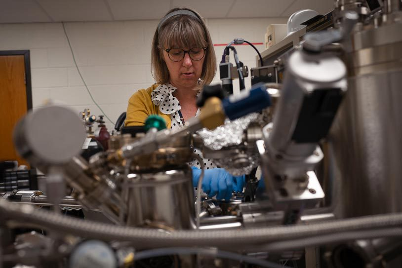 Research scientist Catherine Dukes inserts a vacuum tube into an X-ray photoelectron spectrometer to get a precise look at lunar material. (Photo by Chris Tyree)