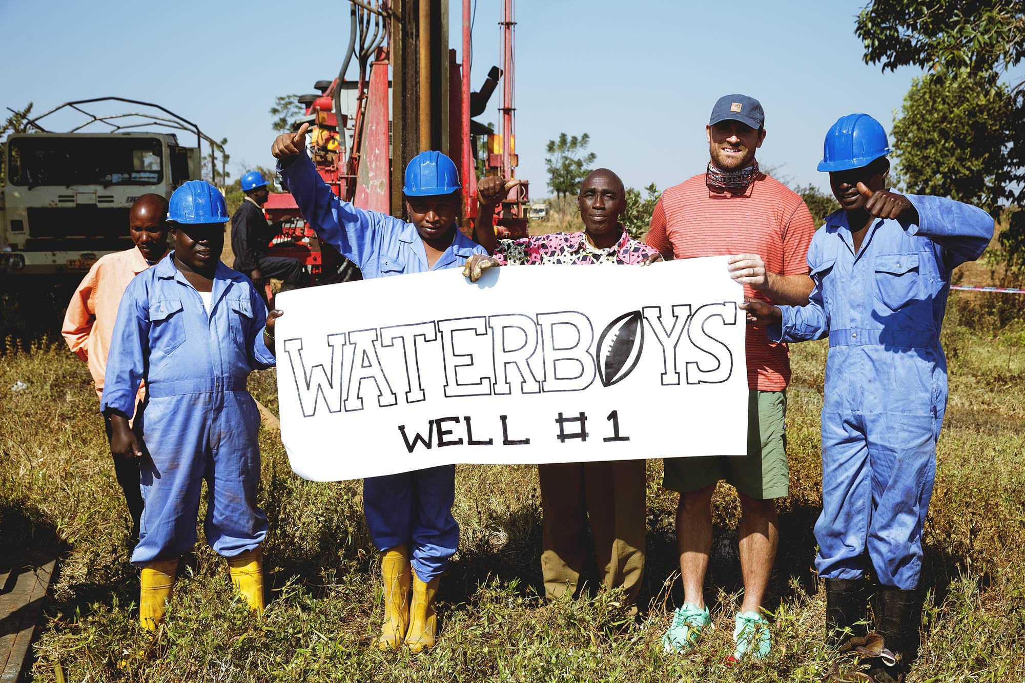 Chris Long, right, celebrates with workers after completing the first well.