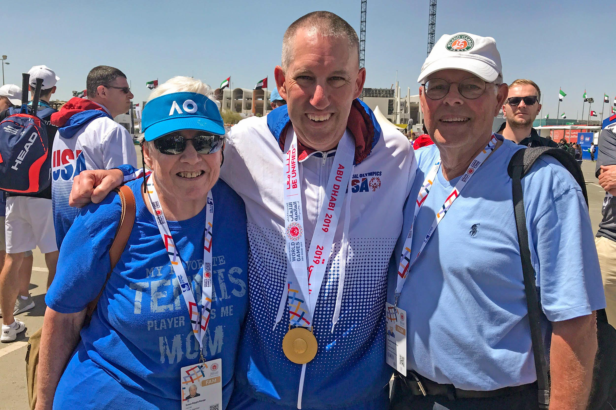 Raupp celebrates his gold-medal victory in Abu Dhabi with his parents, Sue and Lloyd.
