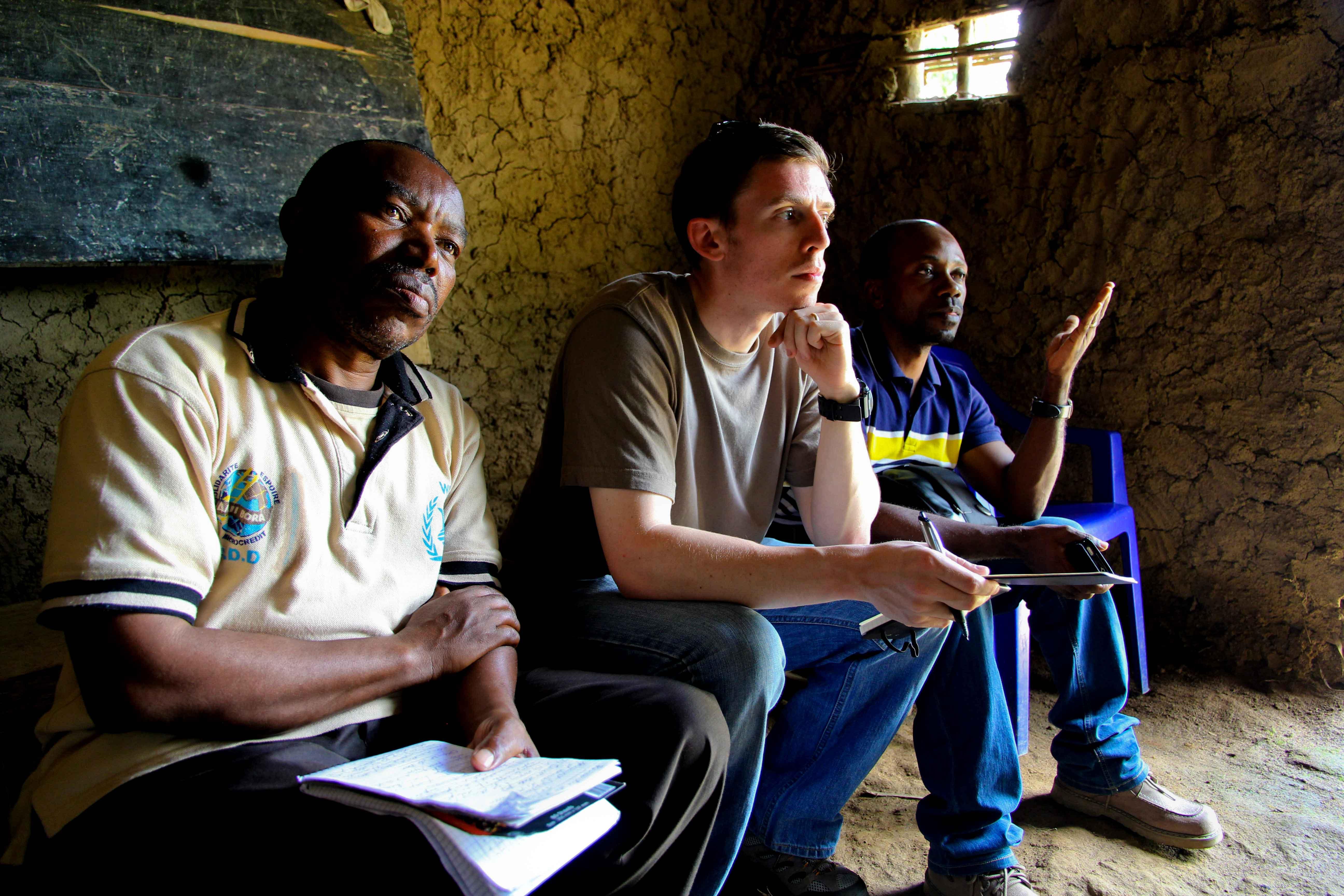 A translator joins Mavuno co-founders Dan Myatt and David Masomo at a meeting of rural community members in eastern Congo.