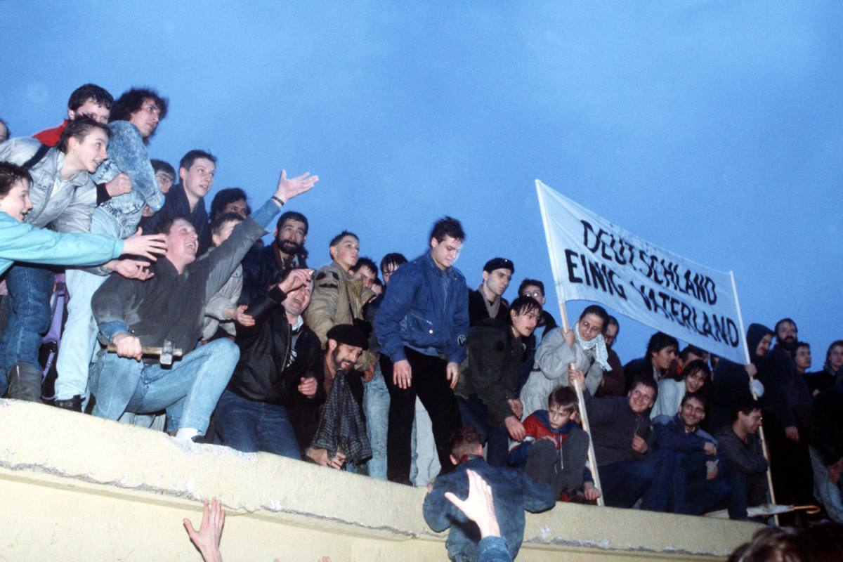 A crowd celebrates atop the Berlin Wall following the official opening of the Brandenburg Gate in 1989.