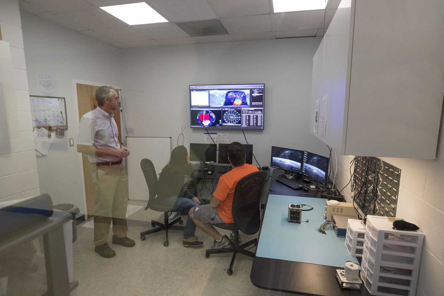 Professor Chris Goyne with students Erin Puckette and Trace LaCour in the CubeSat mission control room at the Engineering School.