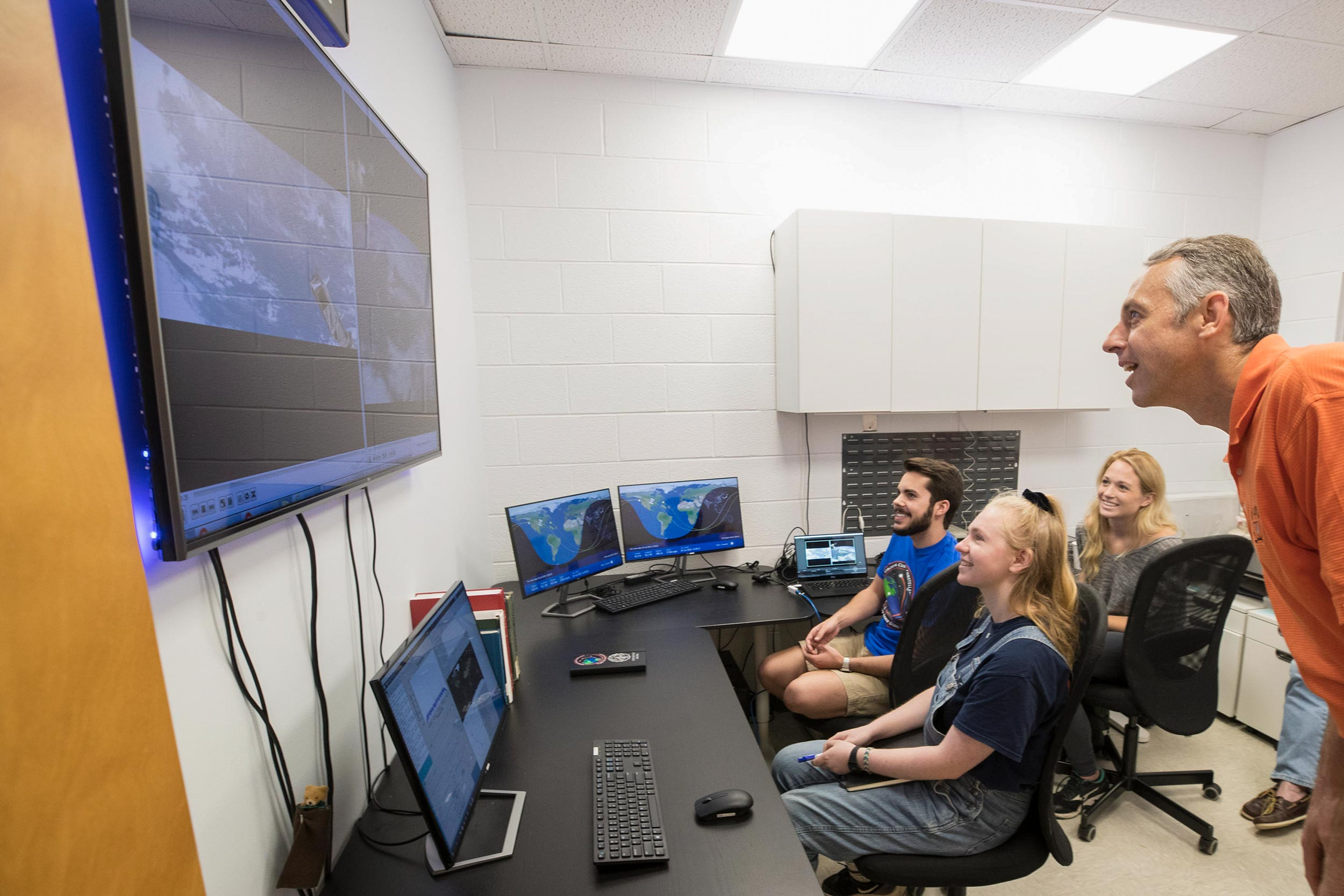 Engineering students Connor Segal, left, Hannah Umansky and Kathryn Wason watch the recent deployment of Libertas from the International Space Station with professor Chris Goyne.