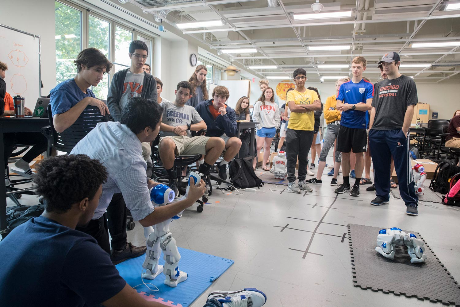 Graduate student Sid Shenoy demonstrates to first-year engineering students how to program the short NAO robots.